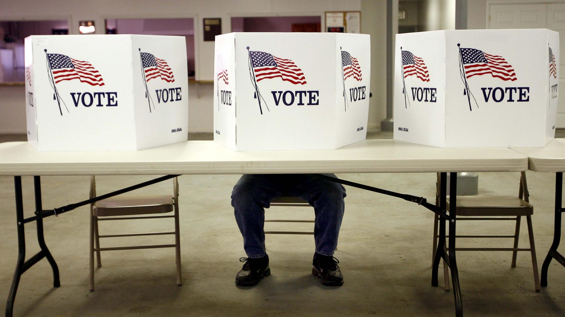 """Una persona esta sentada dentro de una urna de votacion, cubierta con carteles que dicen """"vote"""" y con banderas de los Estados Unidos."""