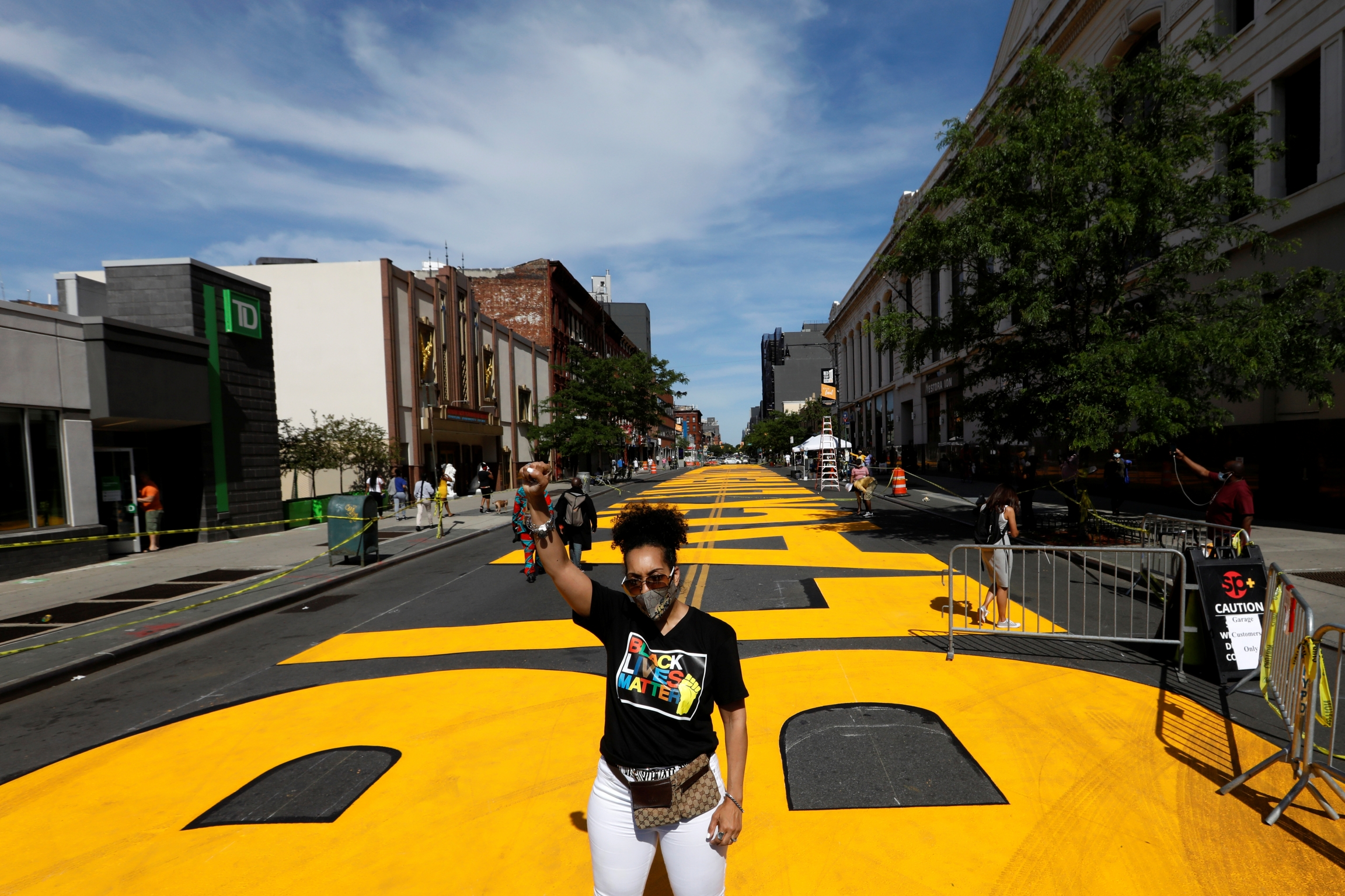 A woman poses in front of a Black Lives Matter mural on the street as a protest against racial inequality in the aftermath of the death in Minneapolis police custody of George Floyd, in Brooklyn, New York, June 16, 2020.