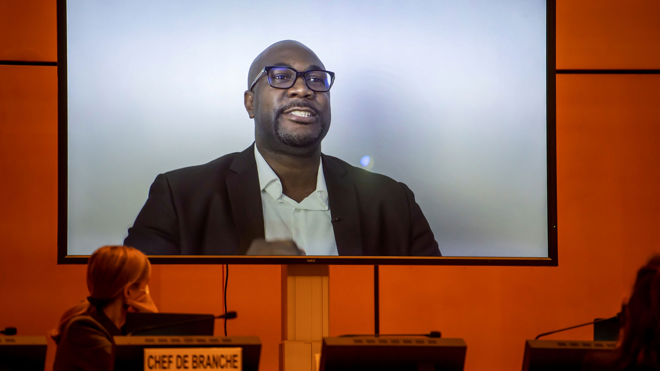 George Floyd's brother, Philonise Floyd, is shown wearing glasses and a blazer while speaking on screen via video message.