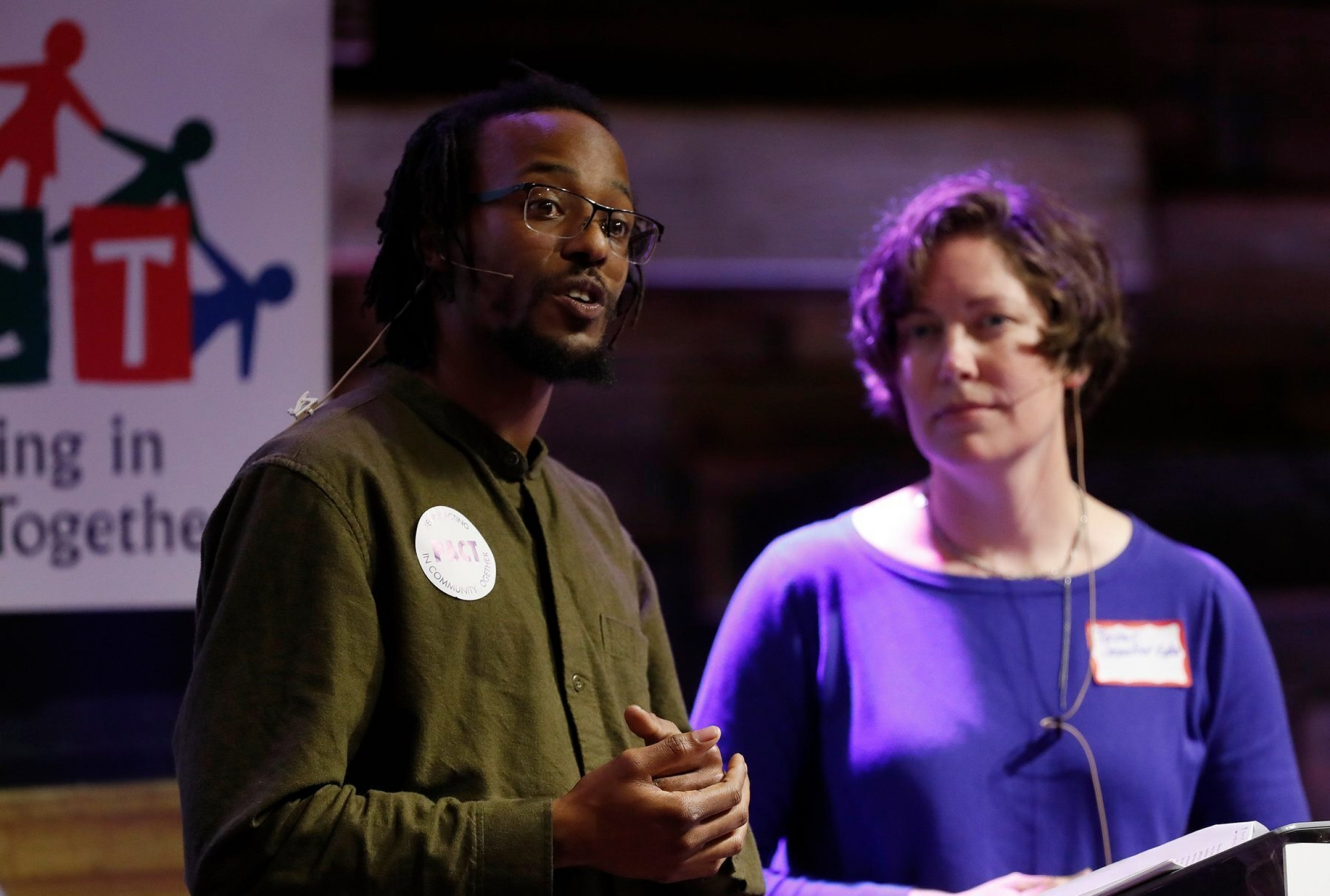 A Black, male community organizer wearing a green shirt speaks next to a white woman wearing a purple shirt at a meeting of People Acting in Community Together in San Jose, California.