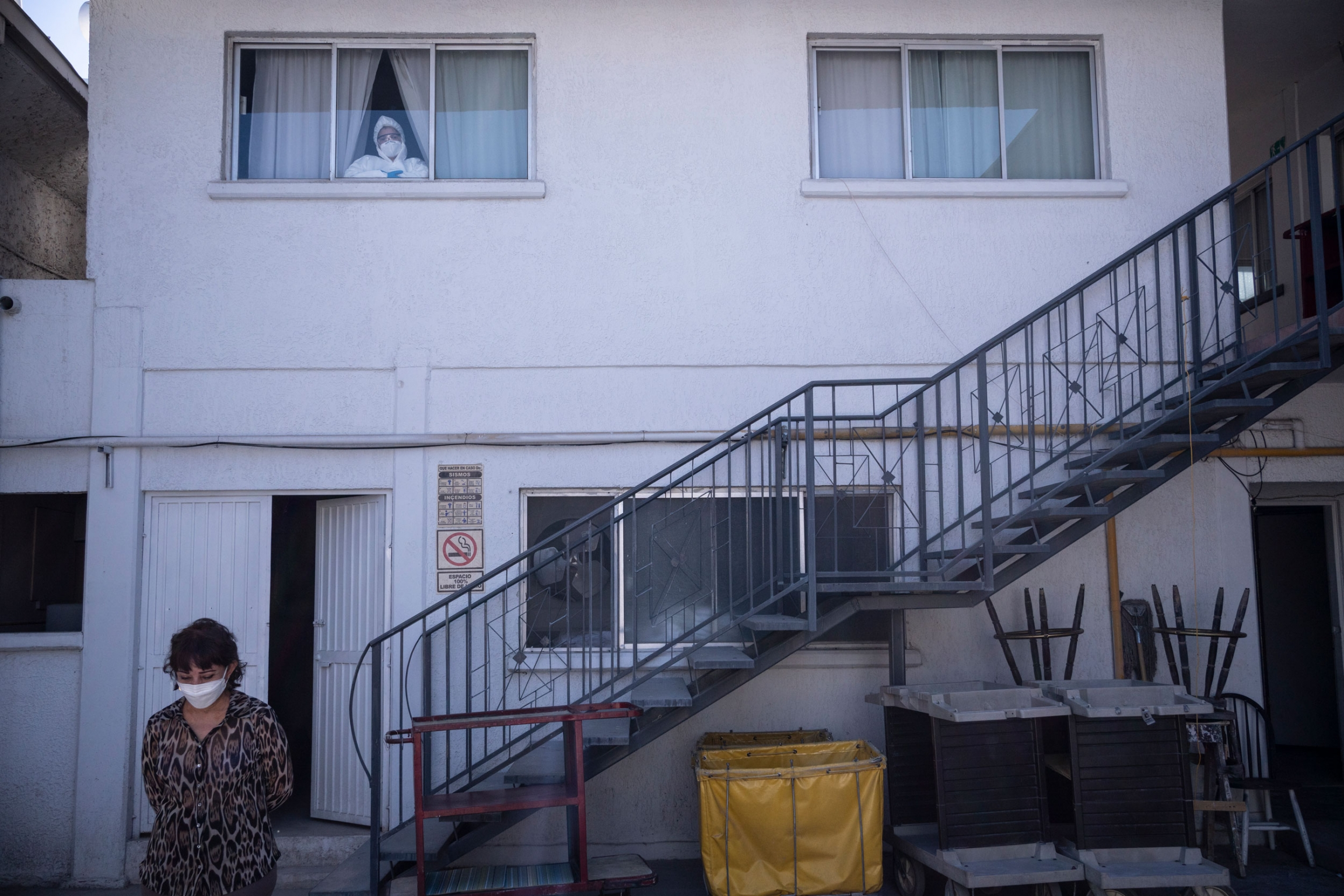 A doctor is shown wearing protective medical clothing and looking through the window on the second floor of a hotel.