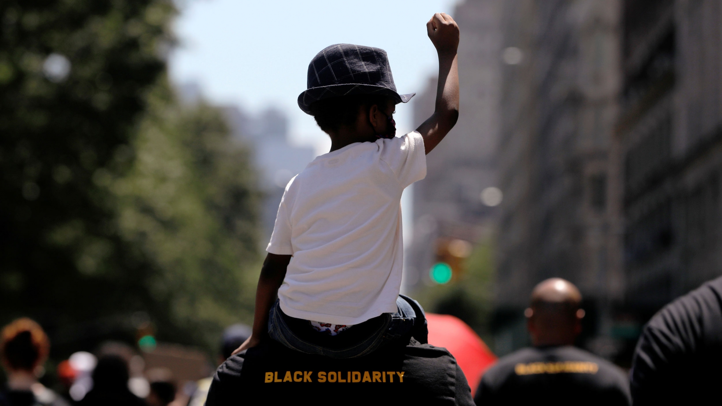 """A young boy is shown wearing a white t-shirt and had while sitting on the shoulder of a man wearing a shirt with """"Black Solidarity"""" printed on it."""