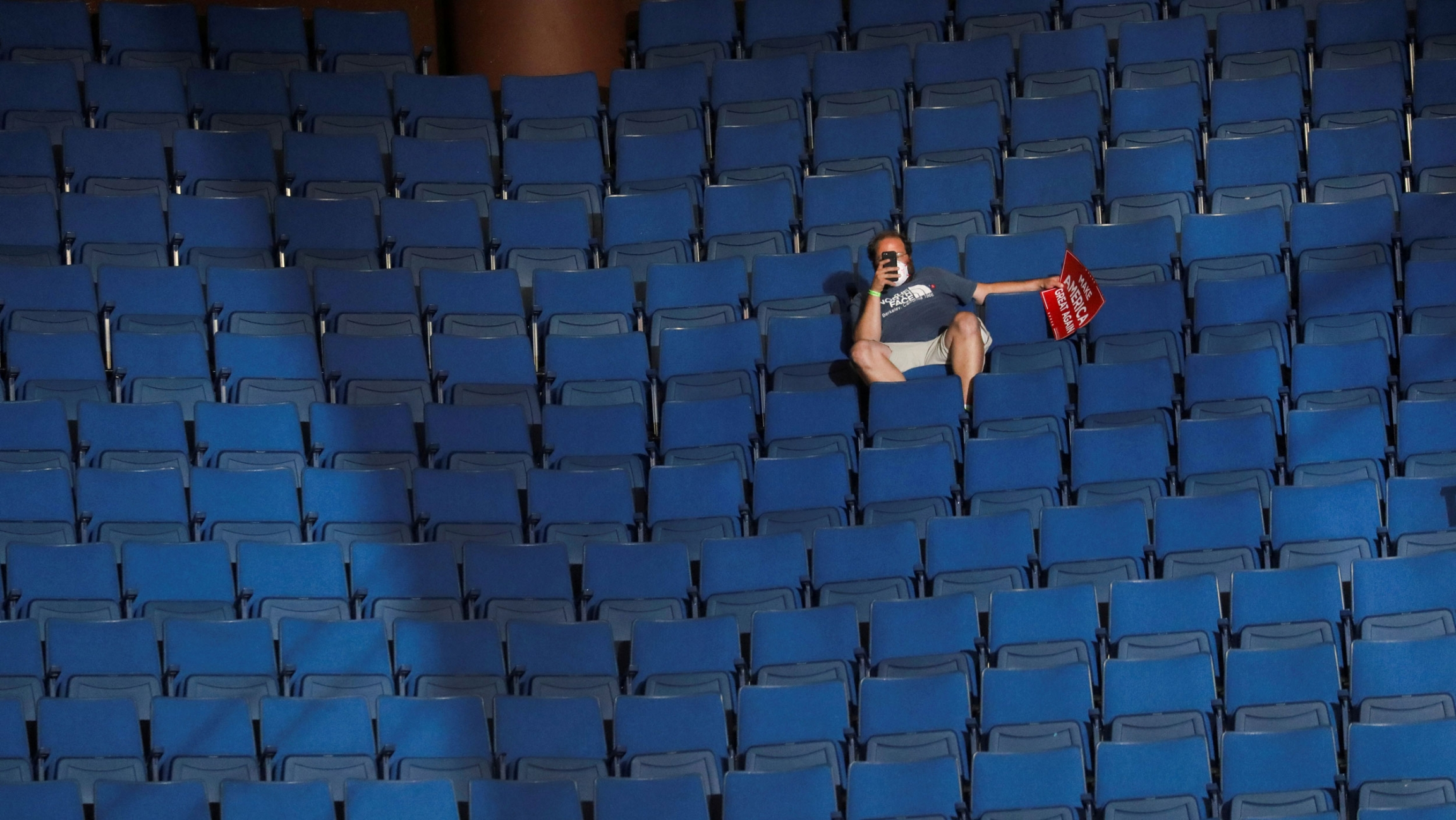 A man is shown sitting in a chairi in an arena hollding his phone up with empty rows of chairs all around him.