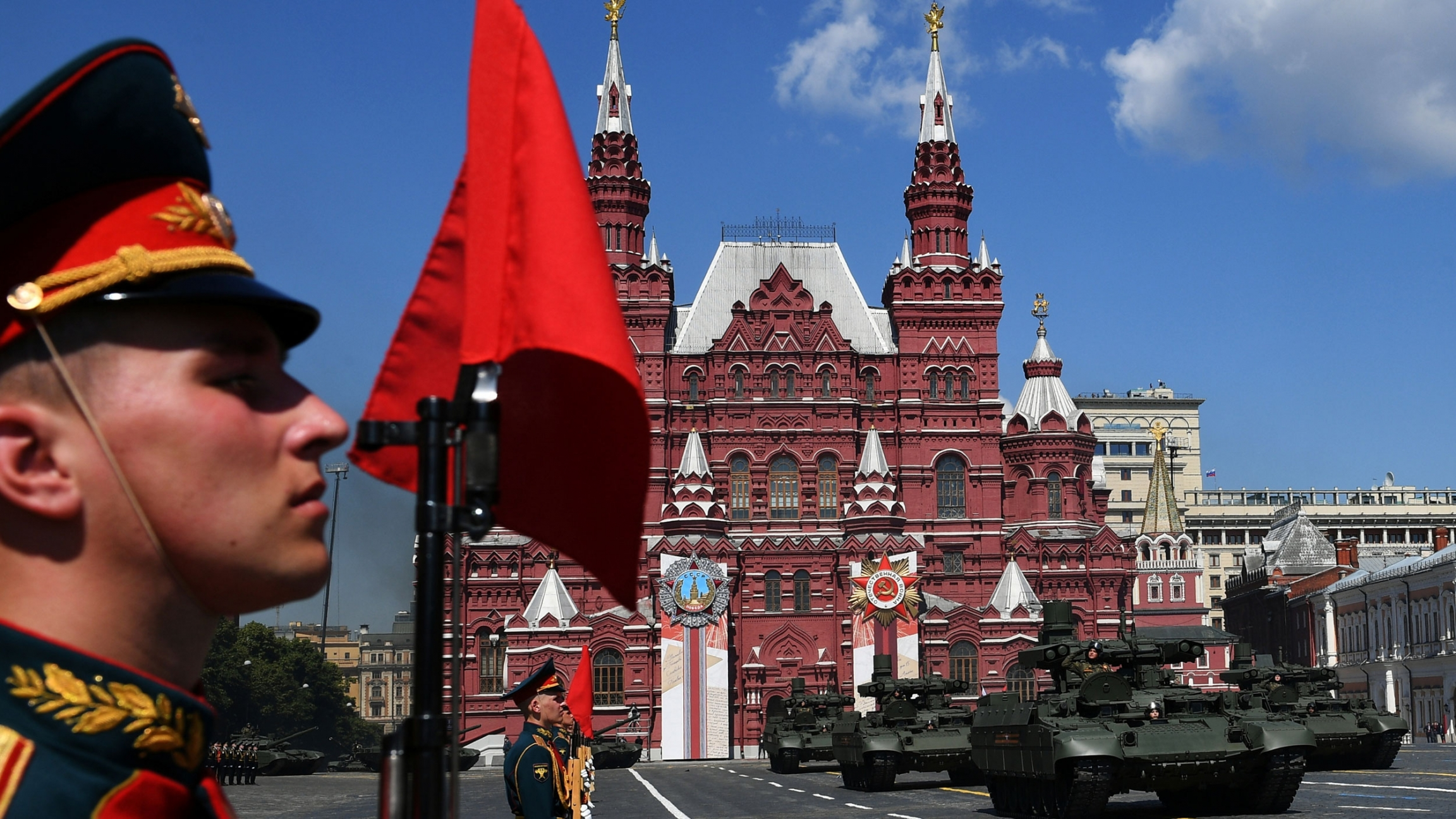 A close up of a man in uniform as tanks drive in Red Square in Moscow