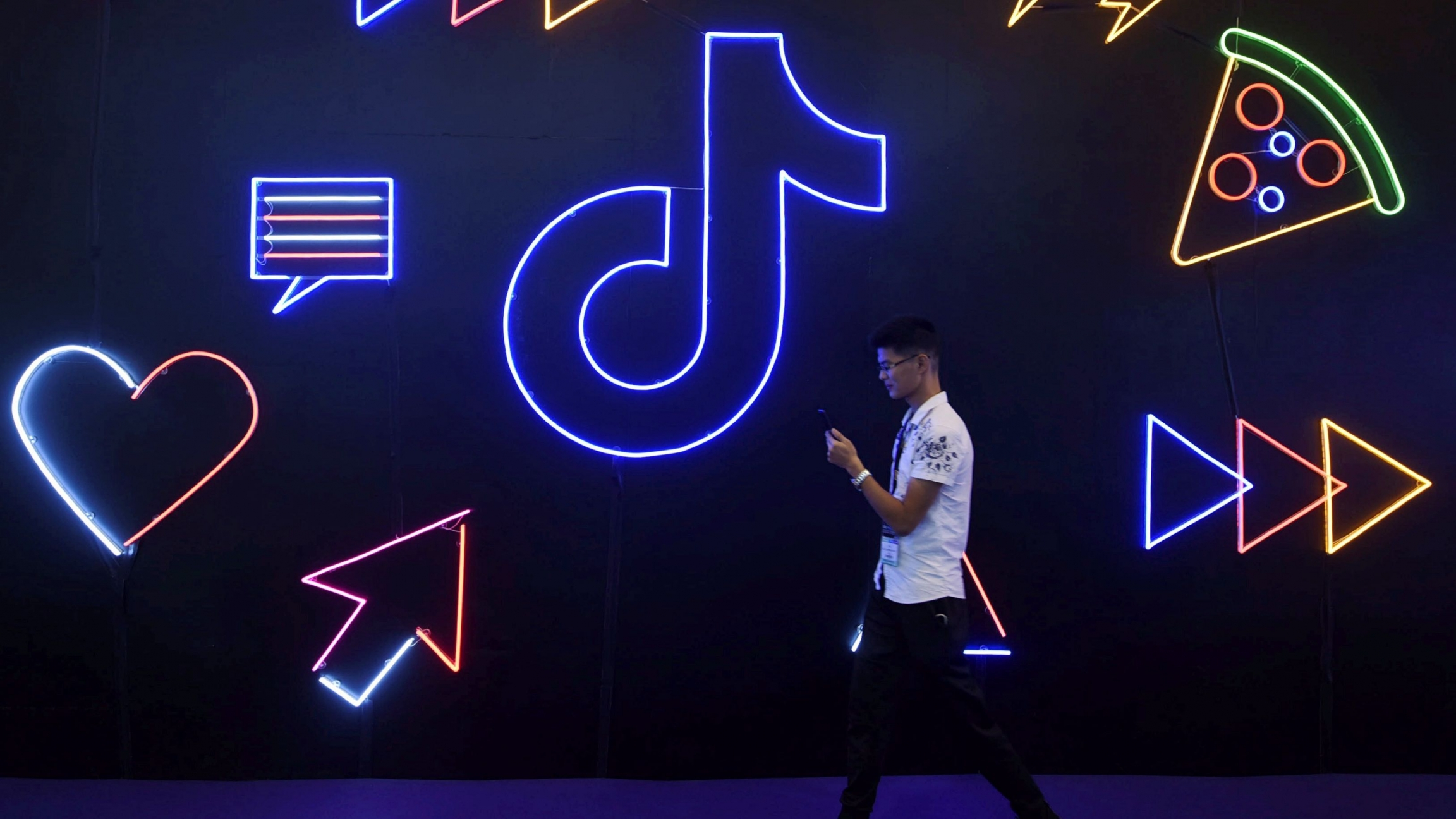 A man holding a phone walks past a sign of Chinese company ByteDance's appTikTok, known locally as Douyin, at the International Artificial Products Expo in Hangzhou, Zhejiang province, China, Oct. 18, 2019.