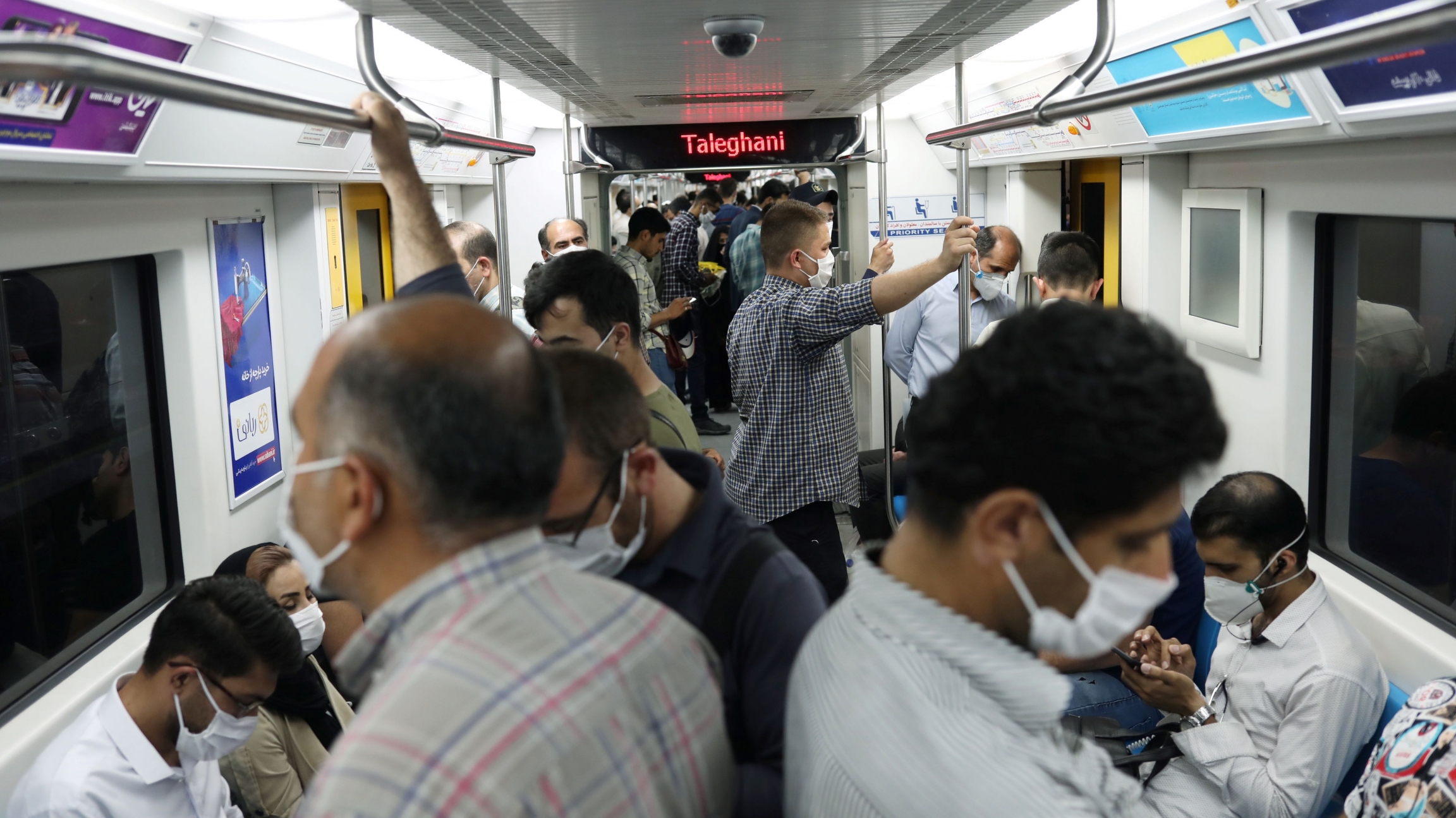 Iranians wear protective face masks while riding on the metro crowded together