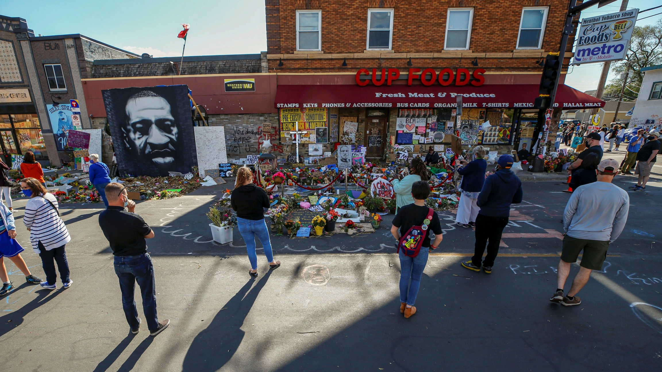 Visitors look at a memorial at the site of the arrest of George Floyd, who died while in police custody, in Minneapolis, June 14, 2020.