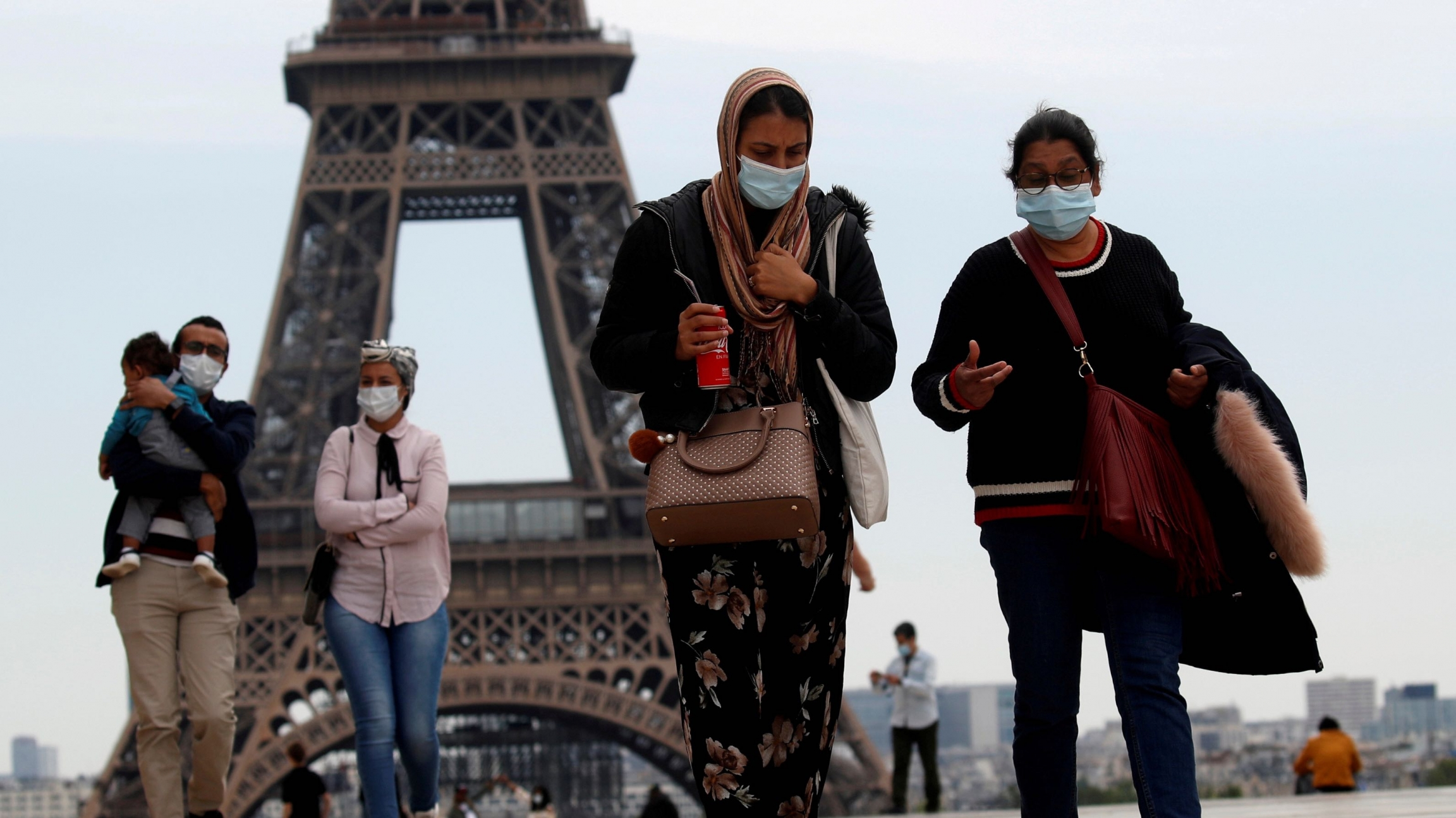 People wearing face masks walk at Trocadero square near the Eiffel Tower, as France began a gradual end to a nationwide lockdown due to the coronavirus disease (COVID-19) in Paris, May 16, 2020.