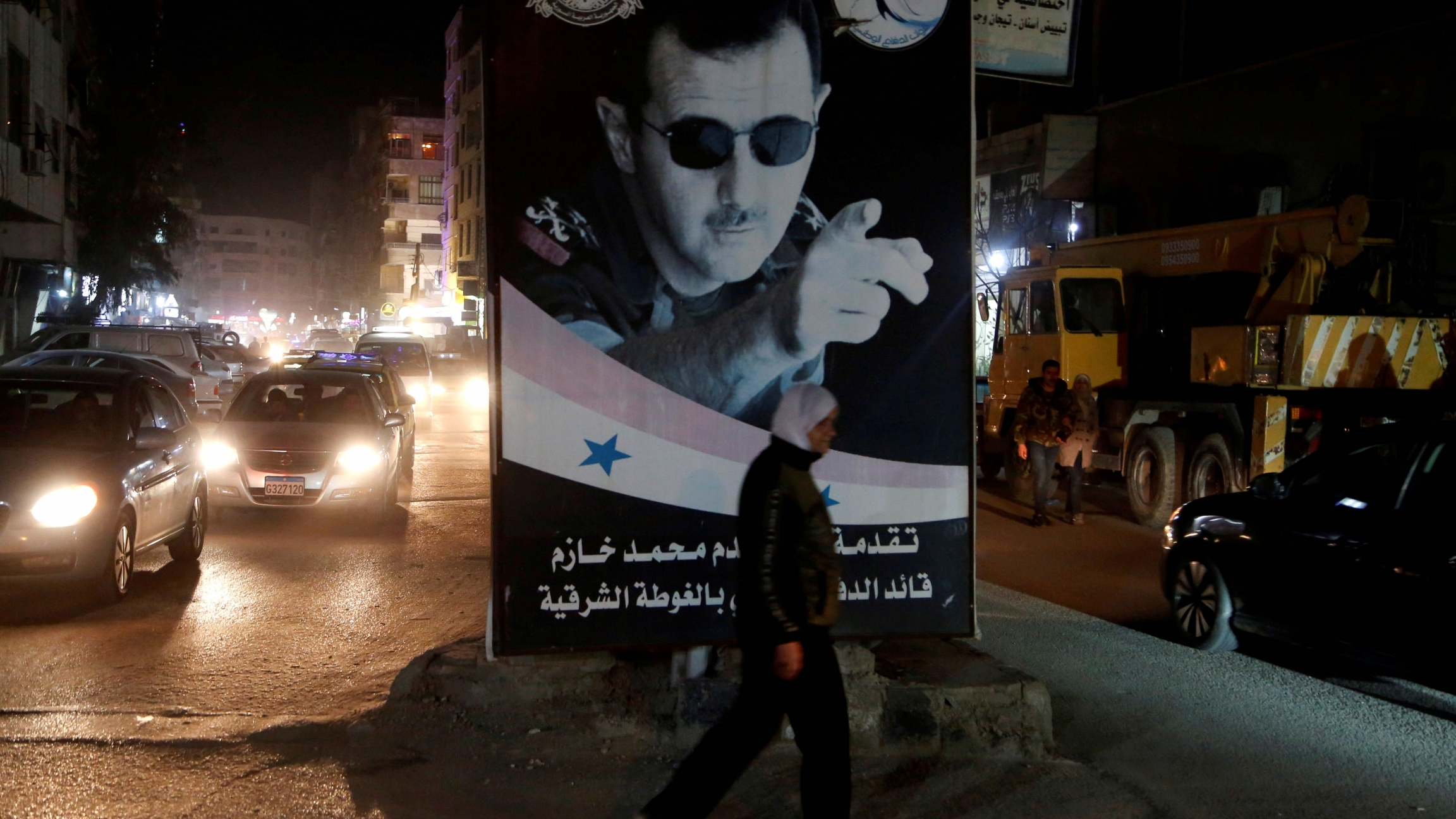 A woman walks past a poster depicting Syria's President Bashar al-Assad in Damascus, Syria, March 5, 2020.