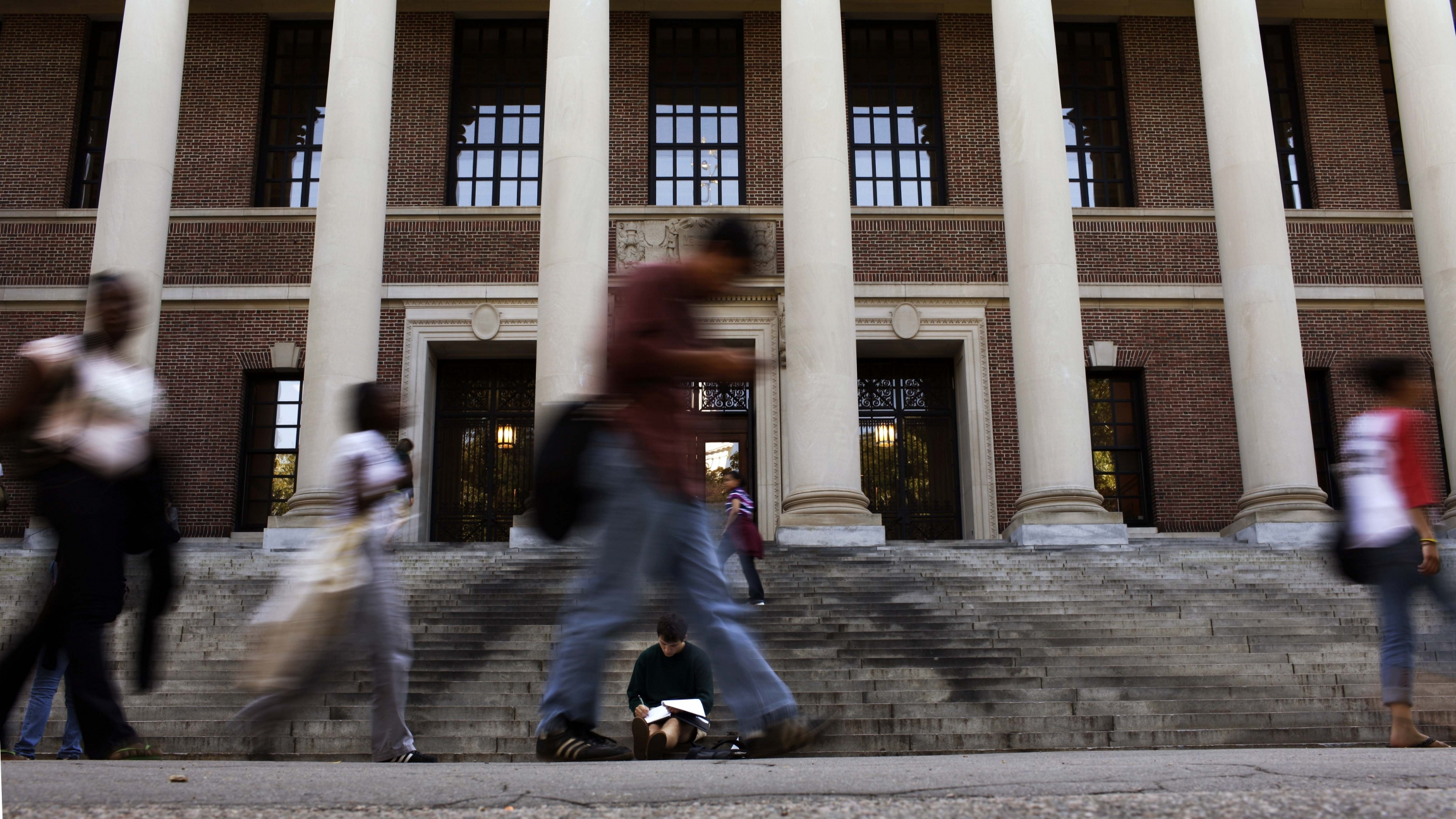 A students sits on the steps of Widener Library at Harvard University in Cambridge, Massachusetts, on Sept. 21, 2009.