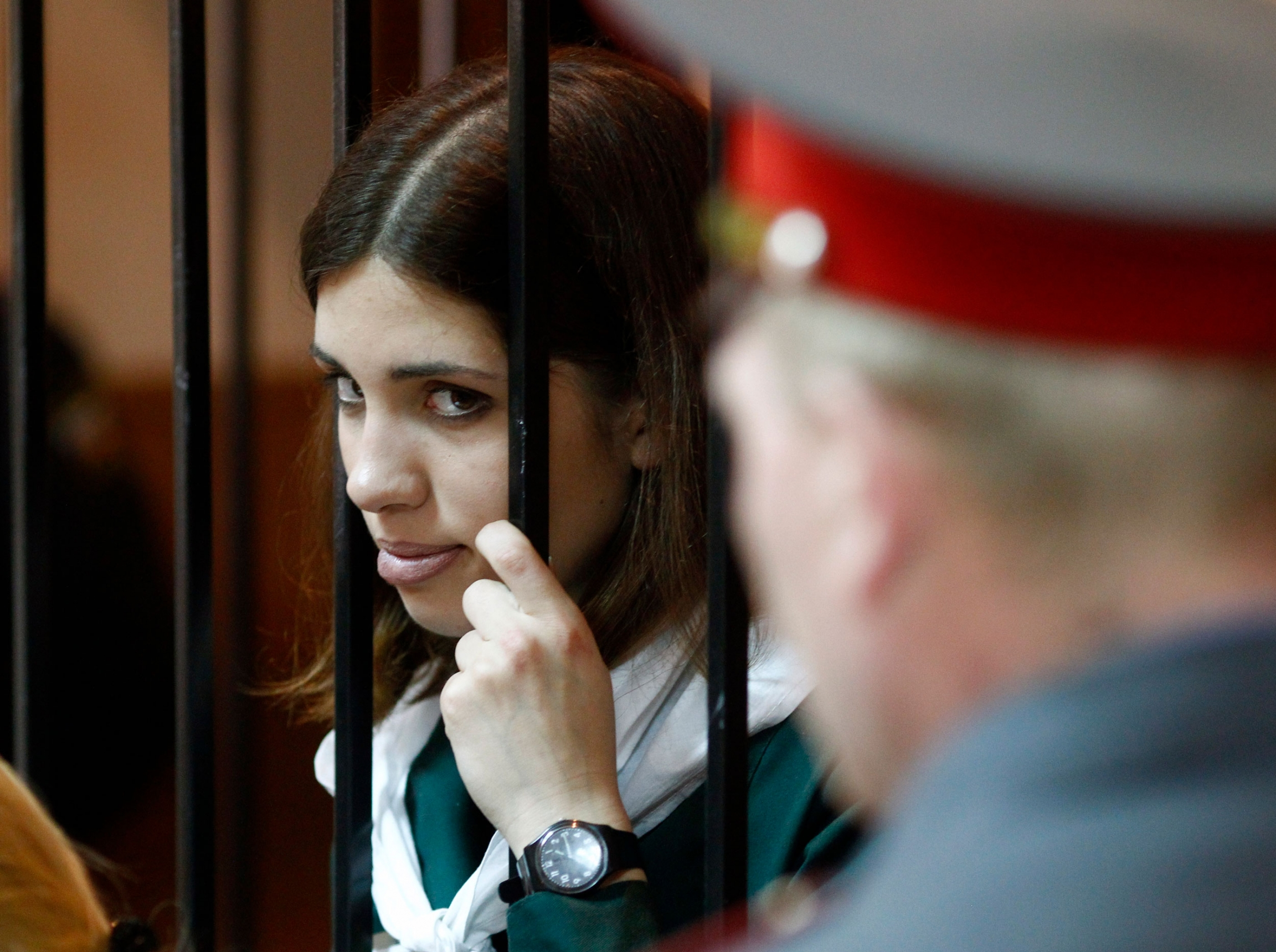 A young woman holds bars of a cell and peers out in a courtroom