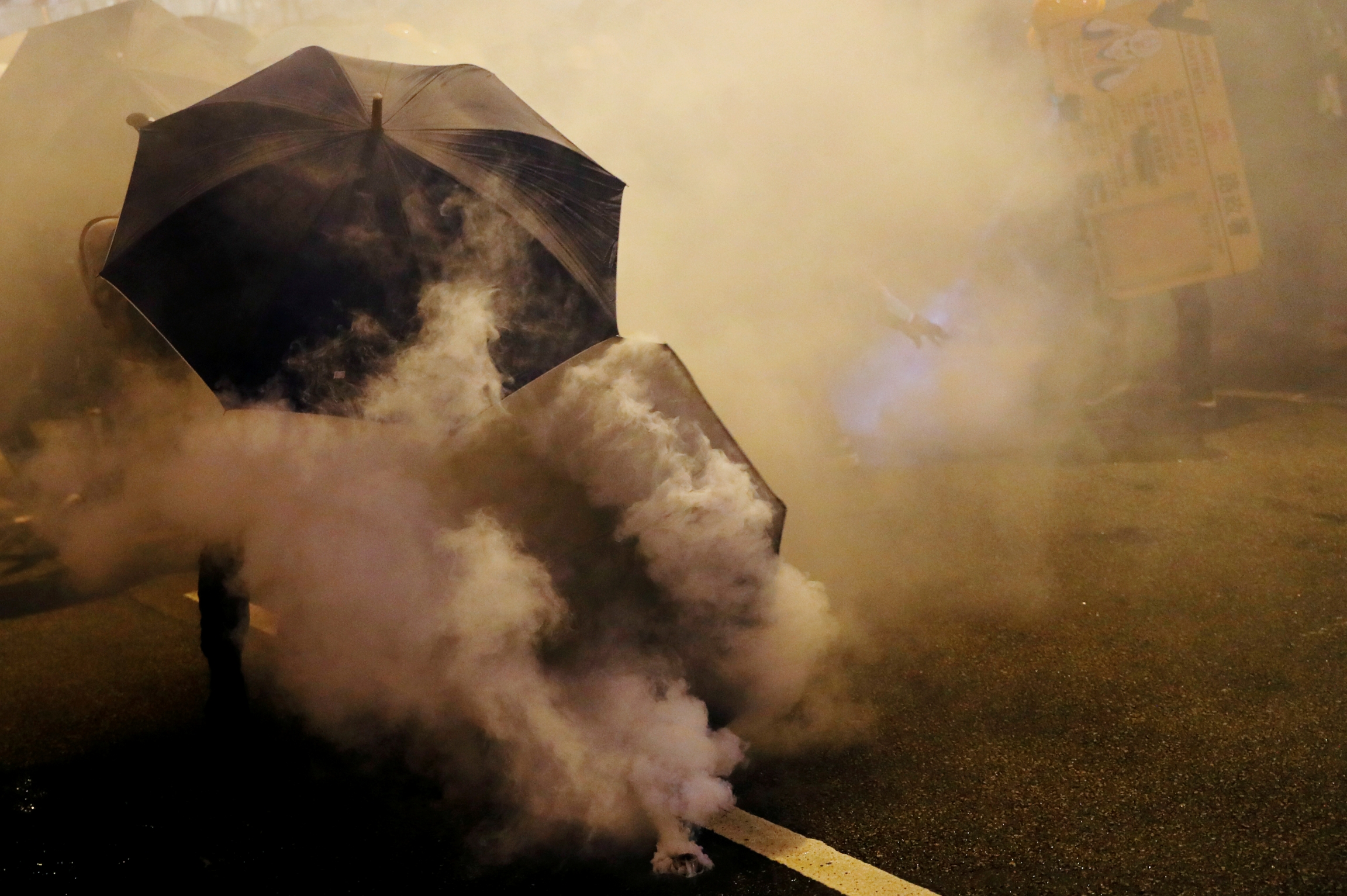 Protesters hold umbrellas in thick tear gas.
