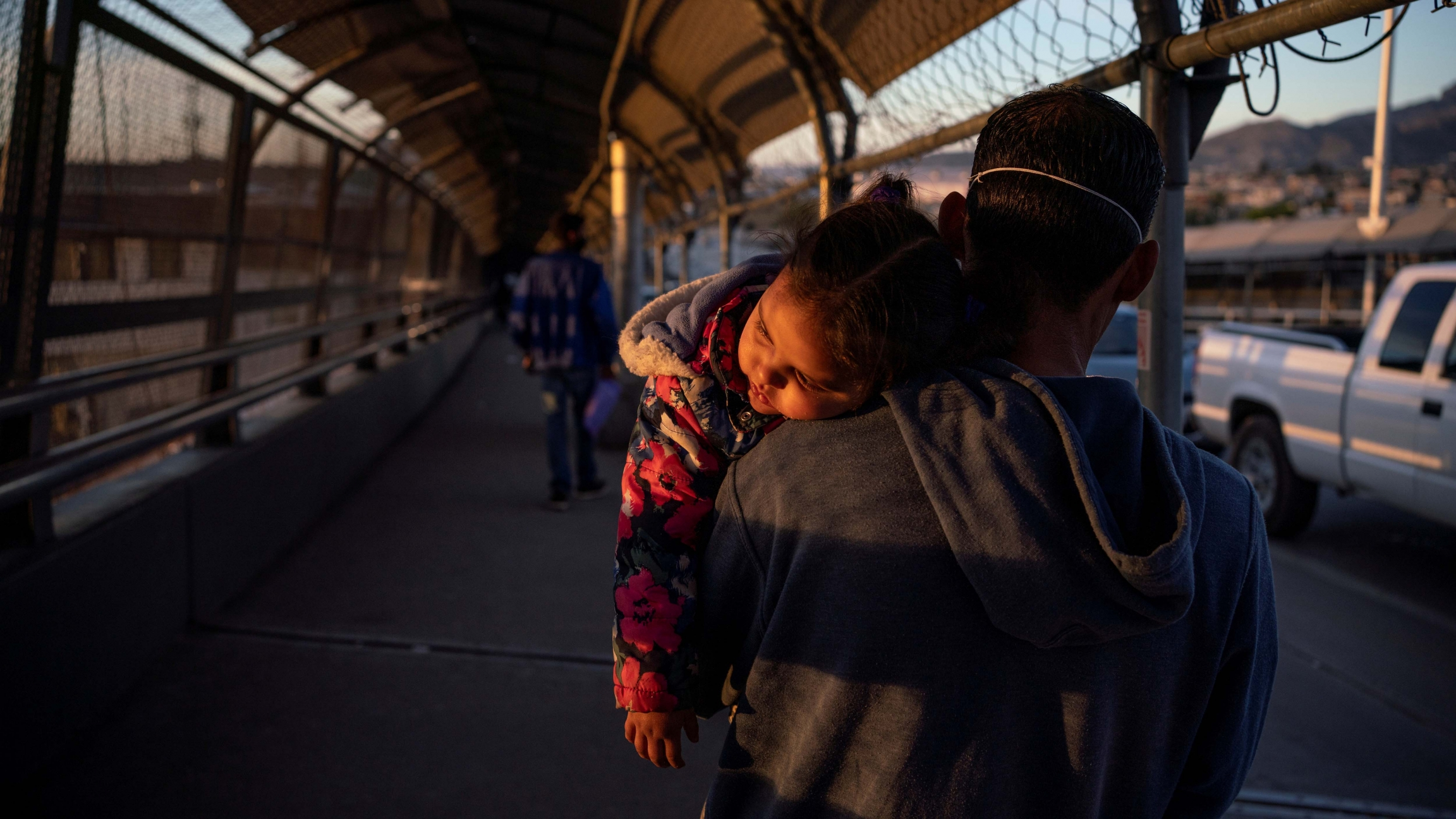A migrant father and child returns to Ciudad Juárez after he had his family's court dates changed by Customs and Border Protection on the Paso del Norte International Bridge after court cancelations amid the coronavirus disease (COVID-19) outbreak in Ciud
