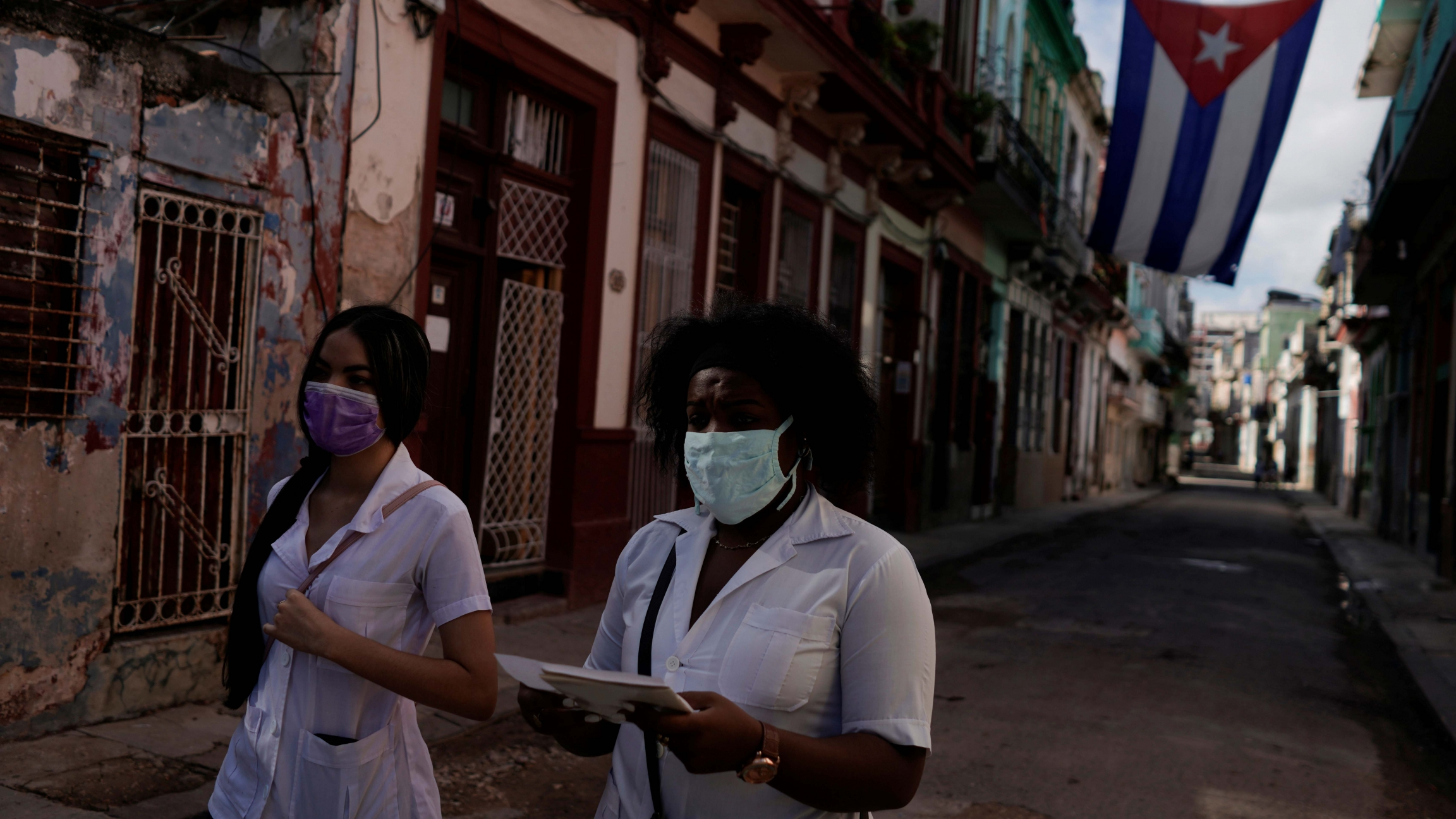 Medical students walk past a Cuban flag as they check door to door for people with symptoms amid concerns about the spread of the coronavirus disease (COVID-19), in downtown Havana, Cuba, May 12, 2020.