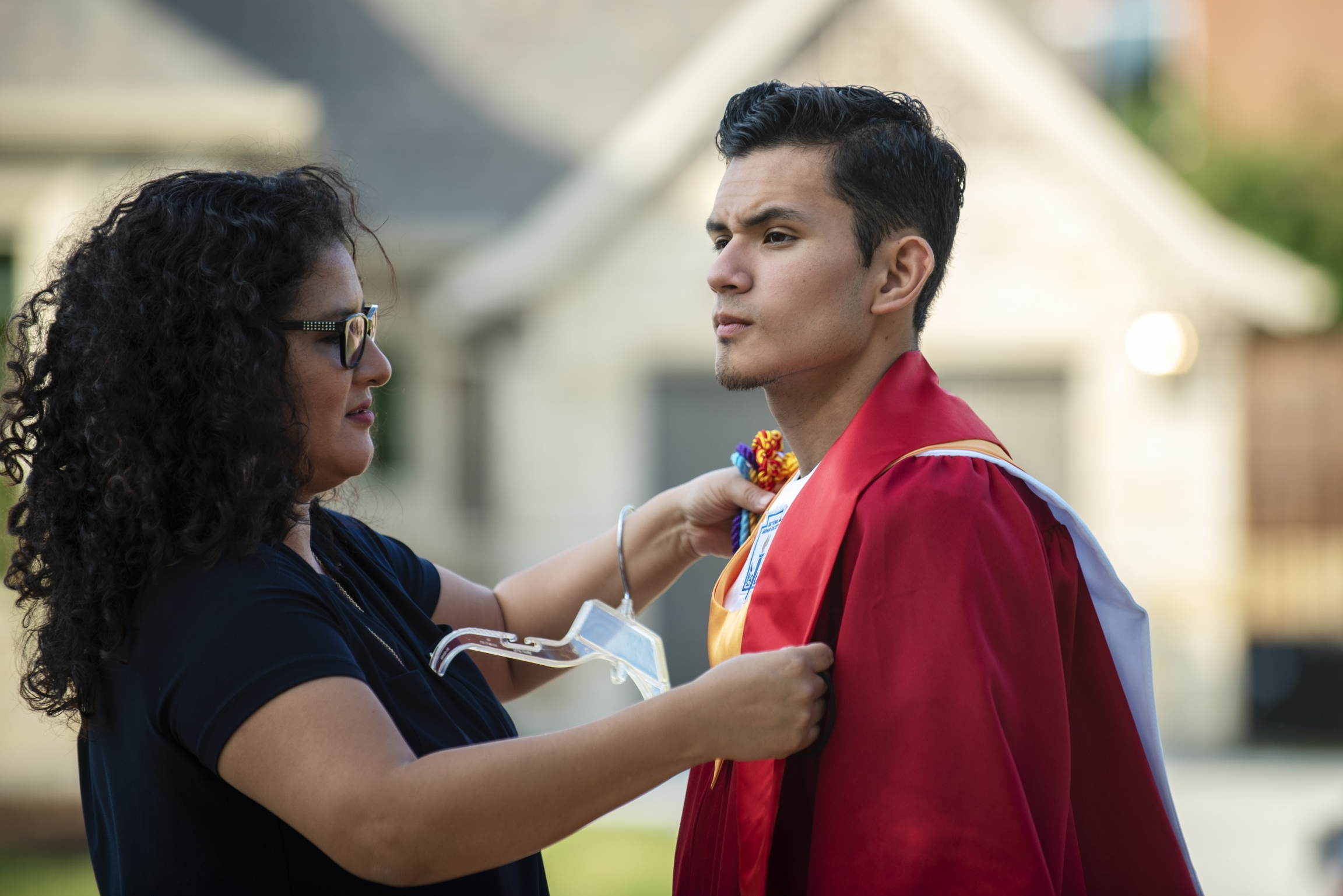Xochitl Ortiz, left, helps her son Izcan Ordaz to try on his graduation gown outside their home in Keller, Texas, May 28, 2020.