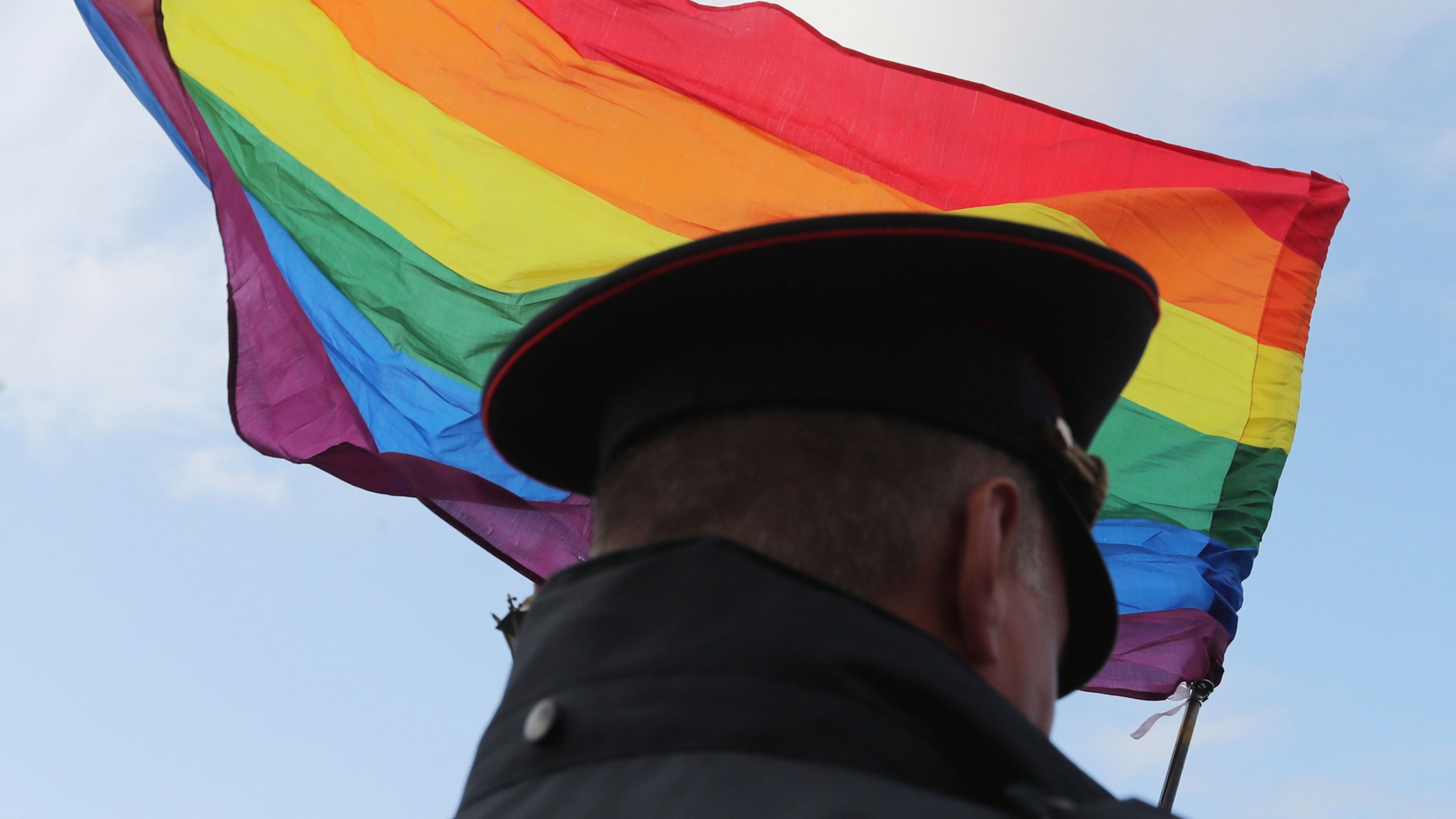 The back of a law enforcement officer's head is silhouetted against a Pride rainbow flag.