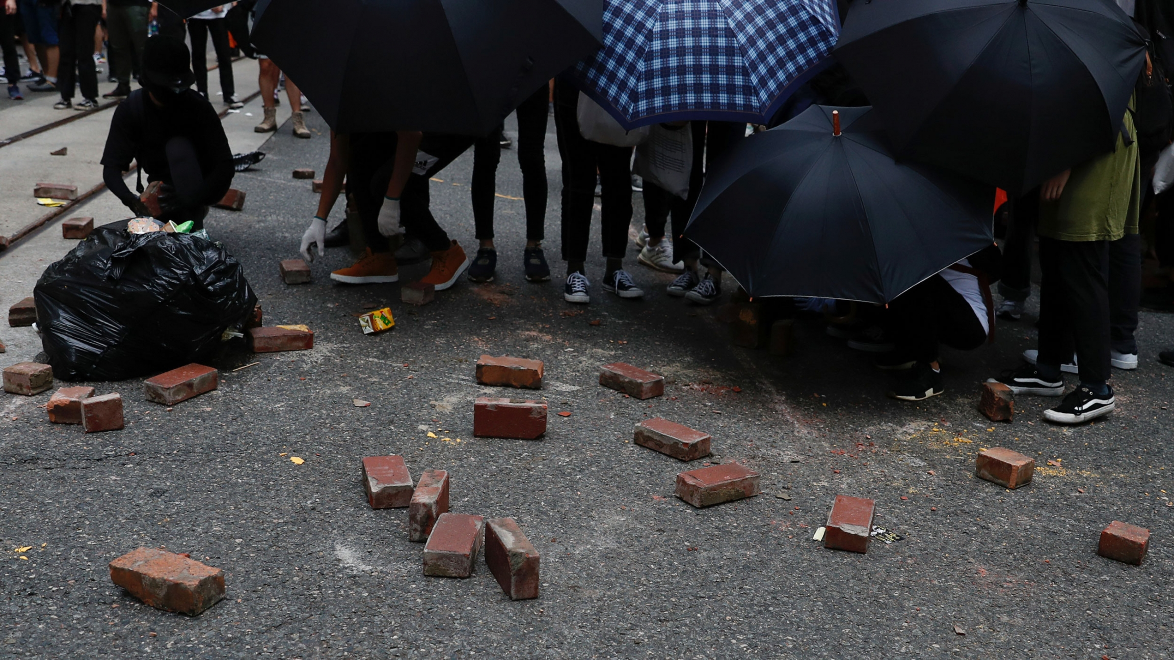 A crowd of people hold umbrellas toward the camera with several bricks laying in the street.