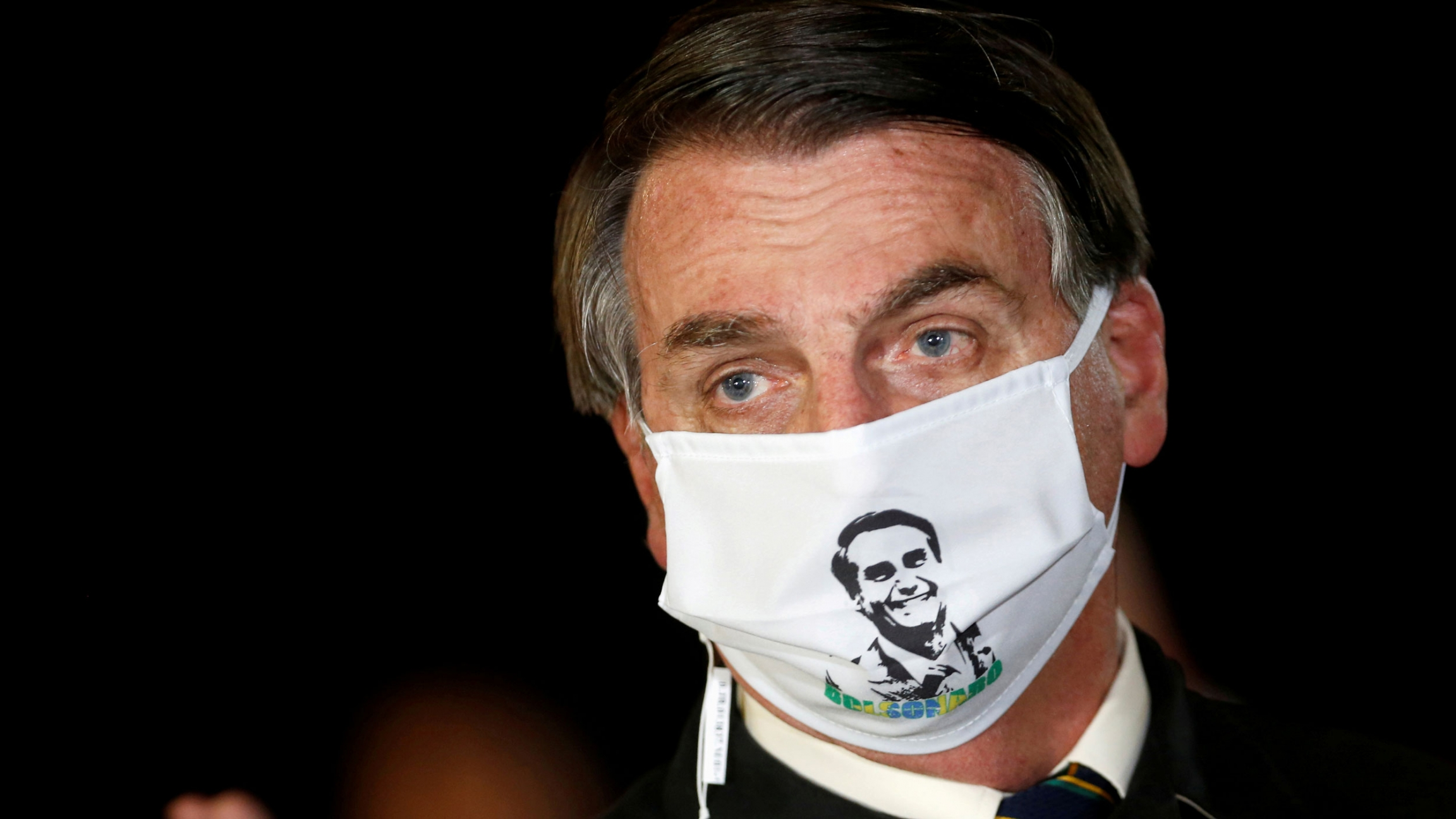 Brazil's President Jair Bolsonaro is shown wearing a white mask with his face printed on it.