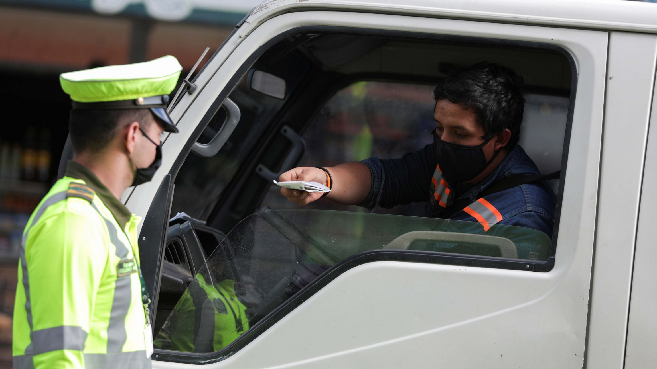 A police officer wearing a face mask asks for identification documents to a driver in one of the neighborhoods where the mayor's office decreed strict quarantine, amidst an outbreak of the coronavirus disease, in Bogota, Colombia, July 14, 2020.
