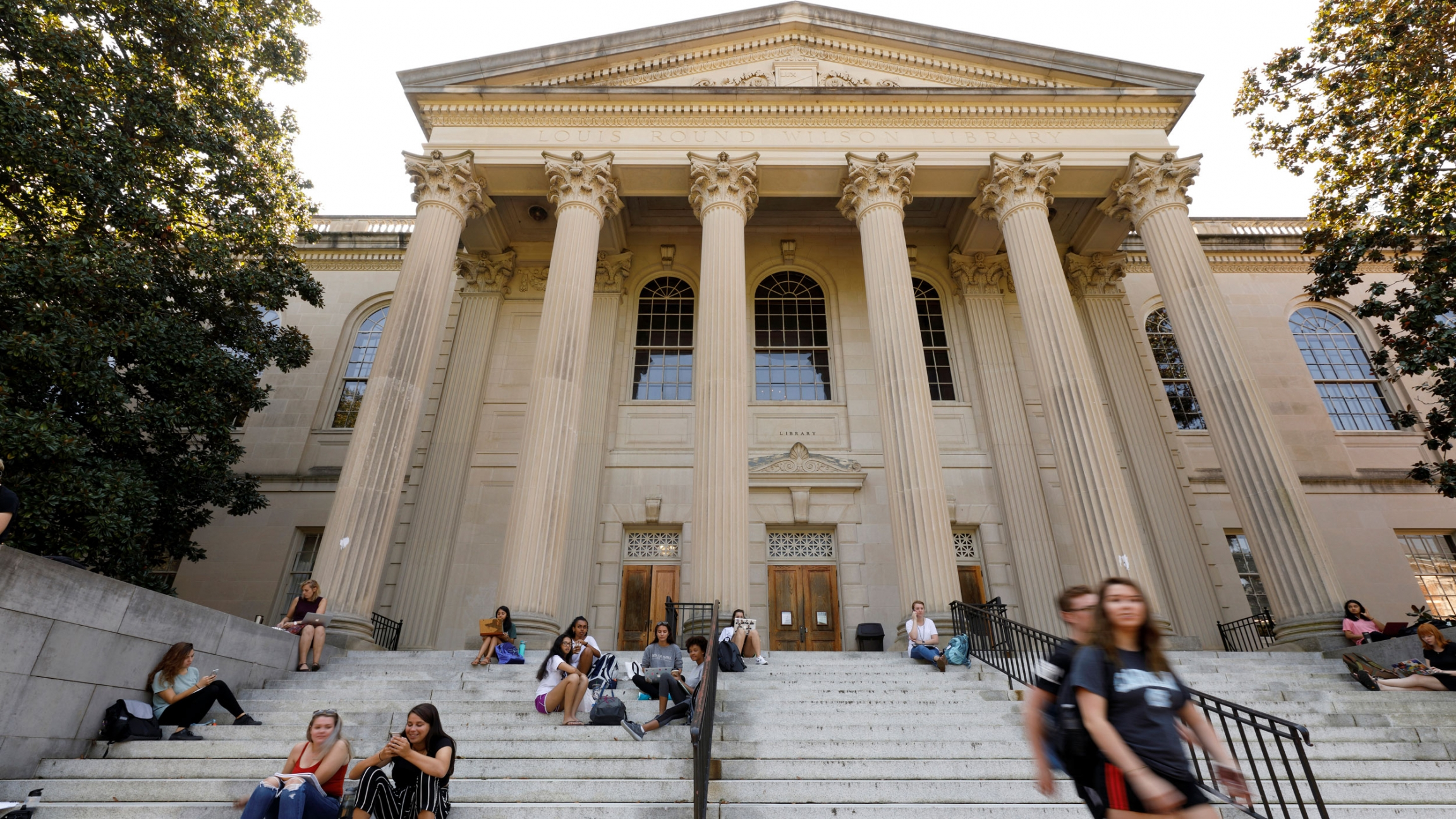 Several students are show sitting on steps with the large Greek columns at the entrance of a college library are shown in the distance.