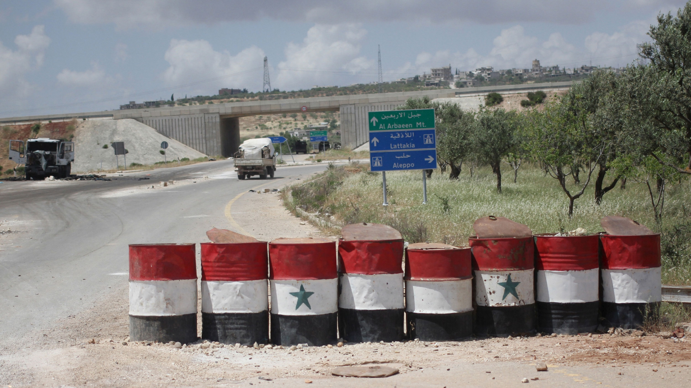 A road is shown with a row of large barrels with the colors of the Syrian flag painted on them.