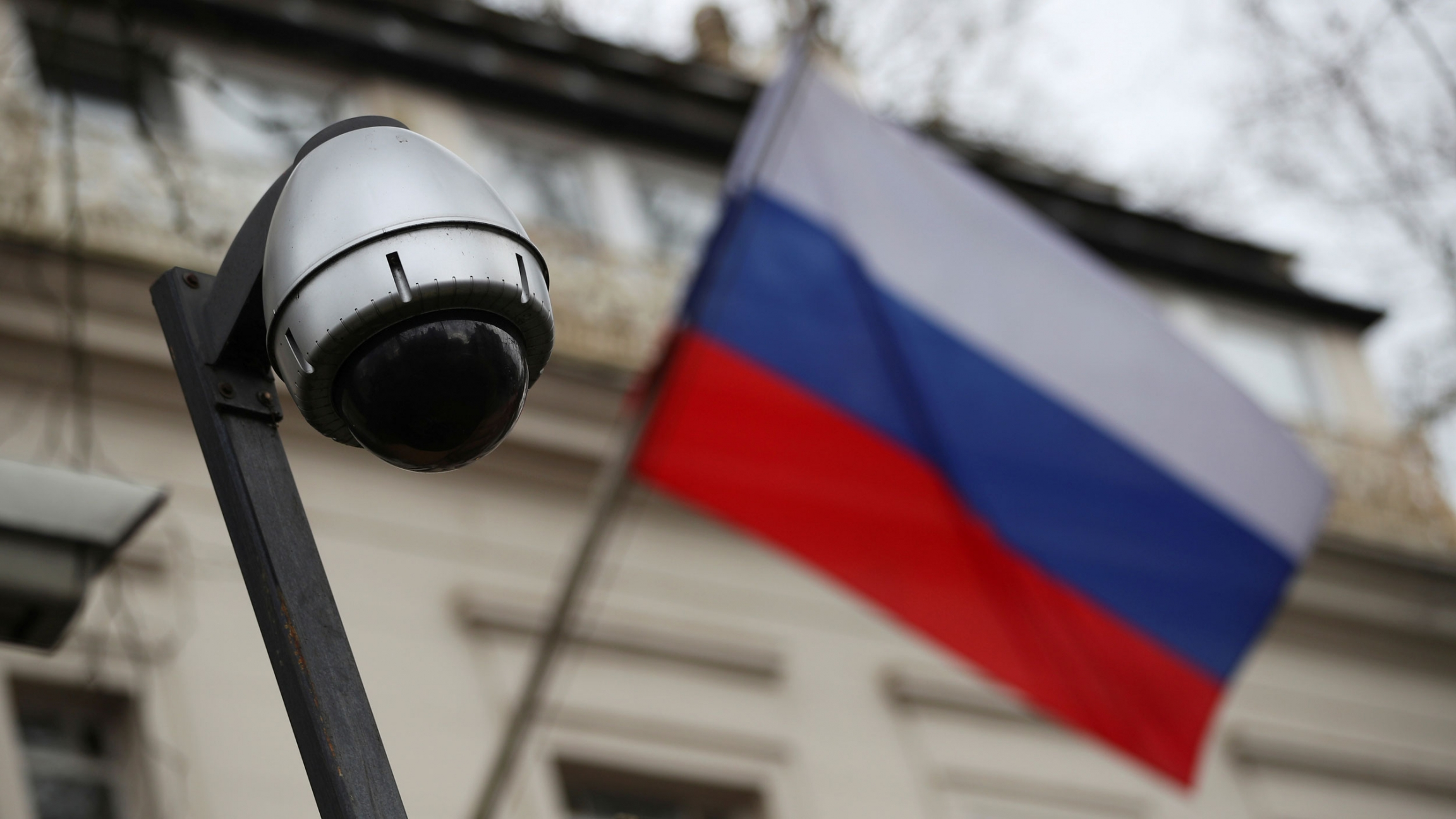 The dark lens of a security camera is shown with a Russian Federation flag in soft focus in the background.