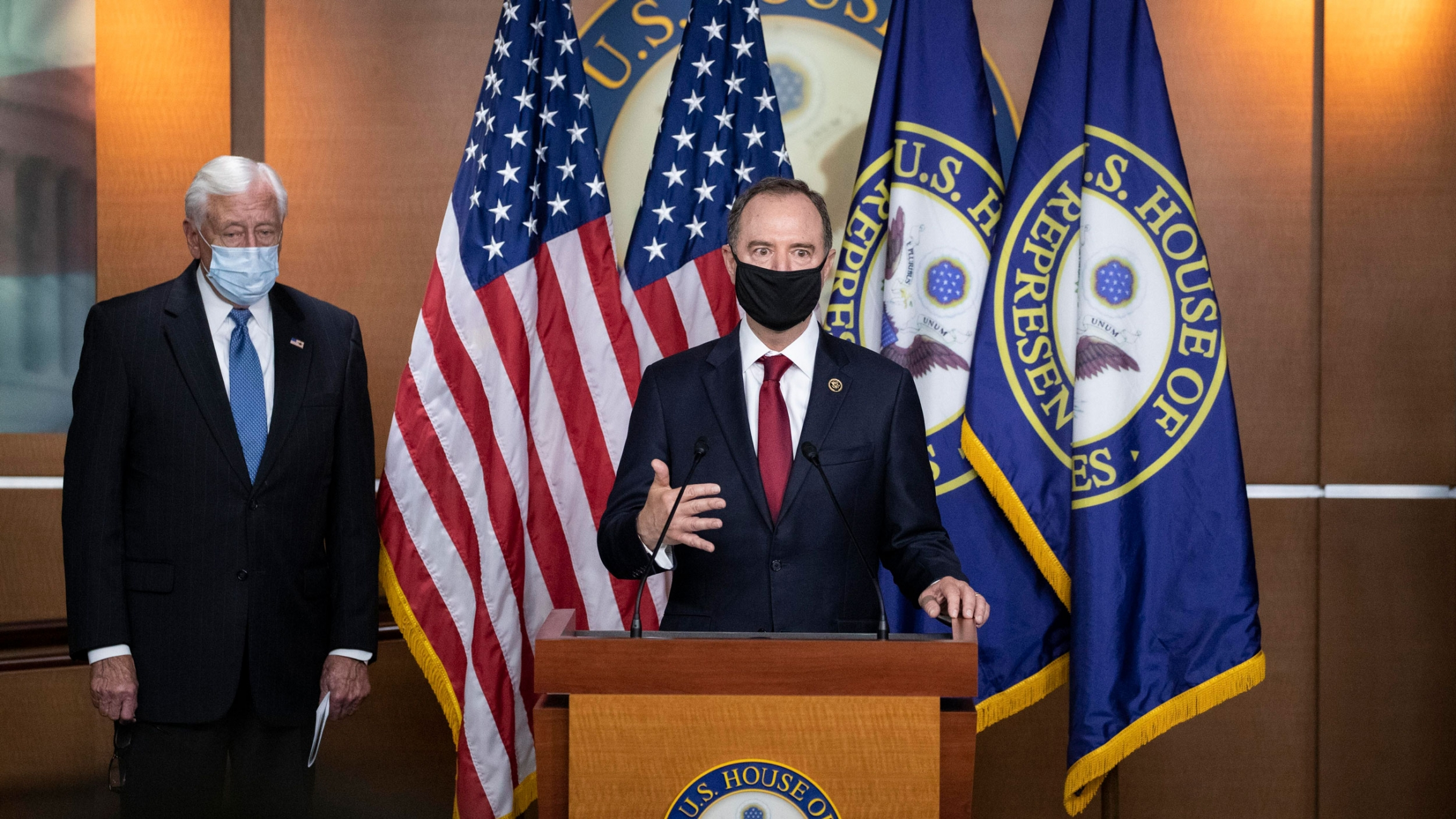 Rep. Adam Schiff is shown wearing a black face mask and standing at a wooden podium with flags behind him.