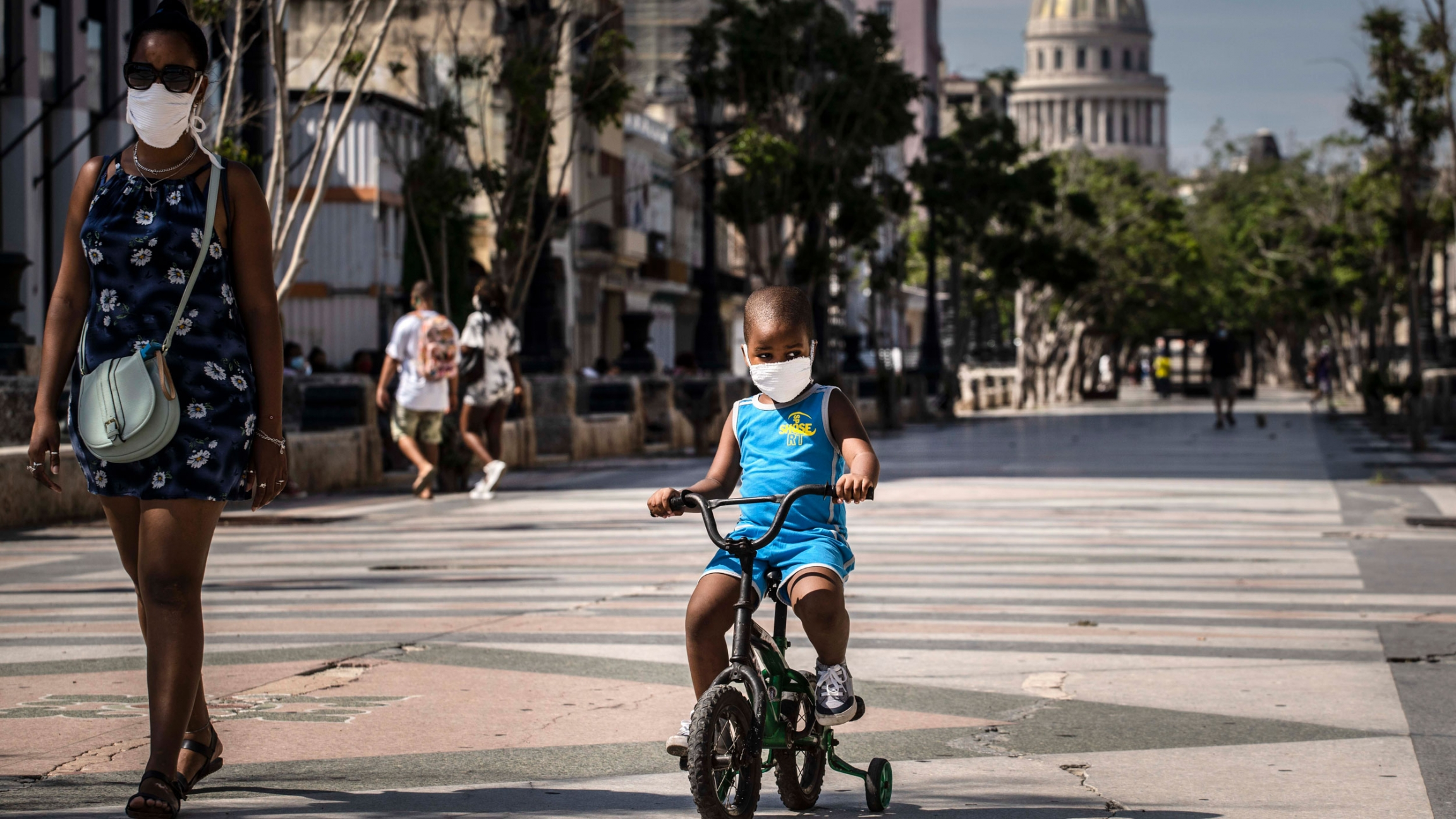 A young child is shown wearing a face mask and a blue outfit and riding a small bicycle with training wheels.