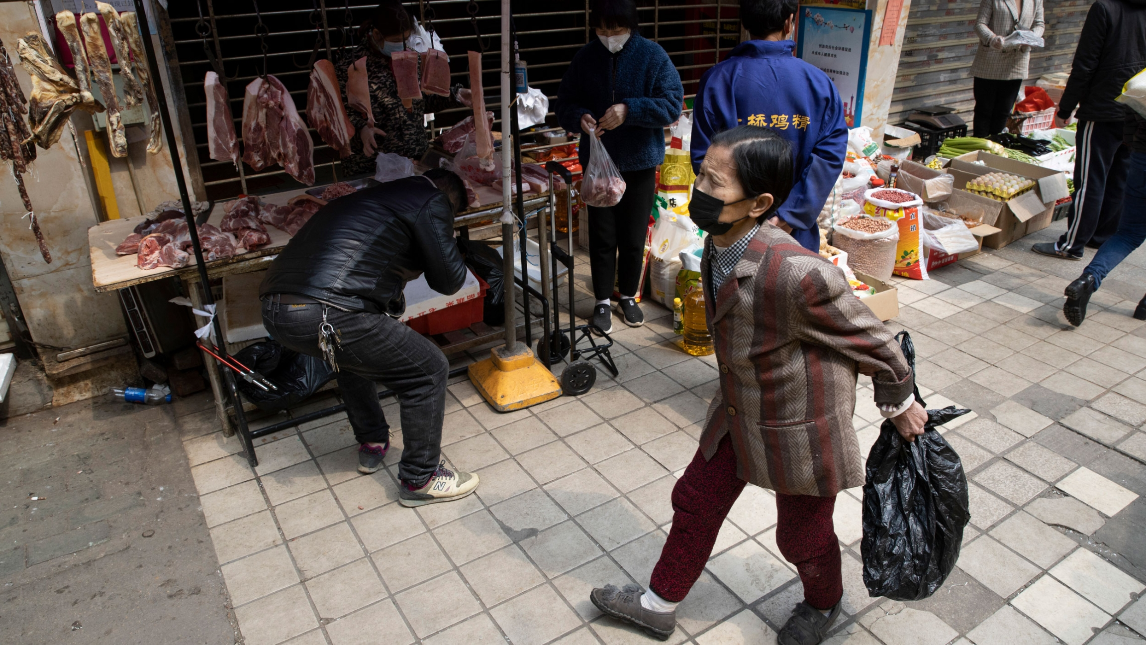 Several people are shown outside of a partially closed market stall with several pieces of meat hanging in the background.