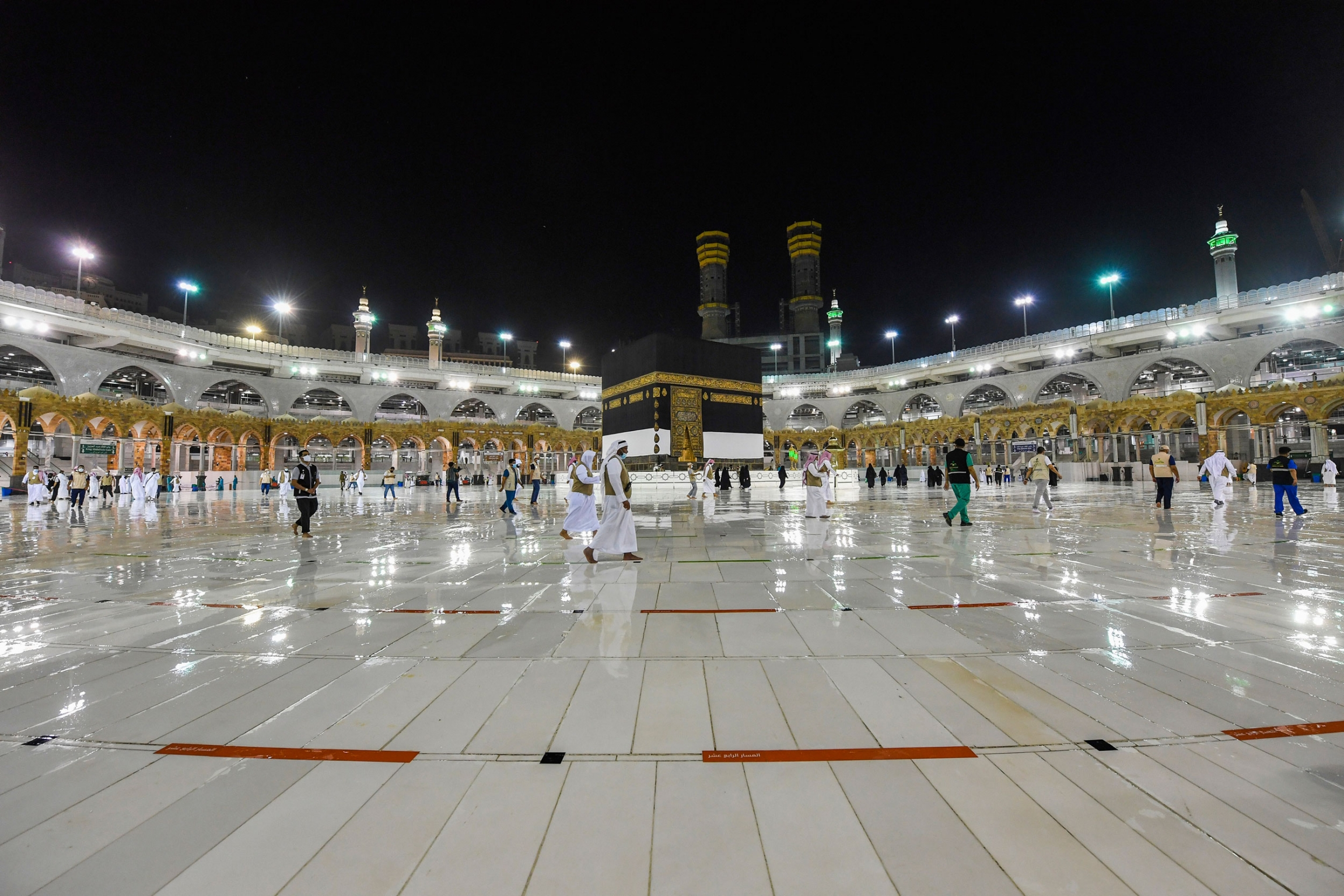 Workers make preparations for the hajj with lights on around the facility showing a shiny floor.