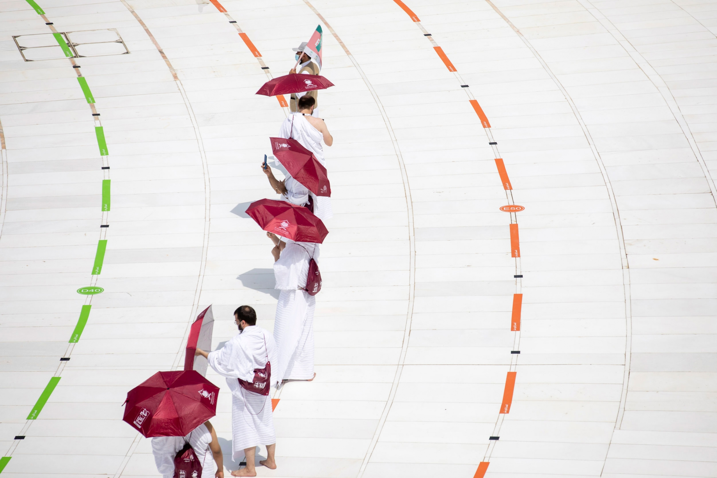 A line of people are shown wearing white robes and carrying red umbrellas.