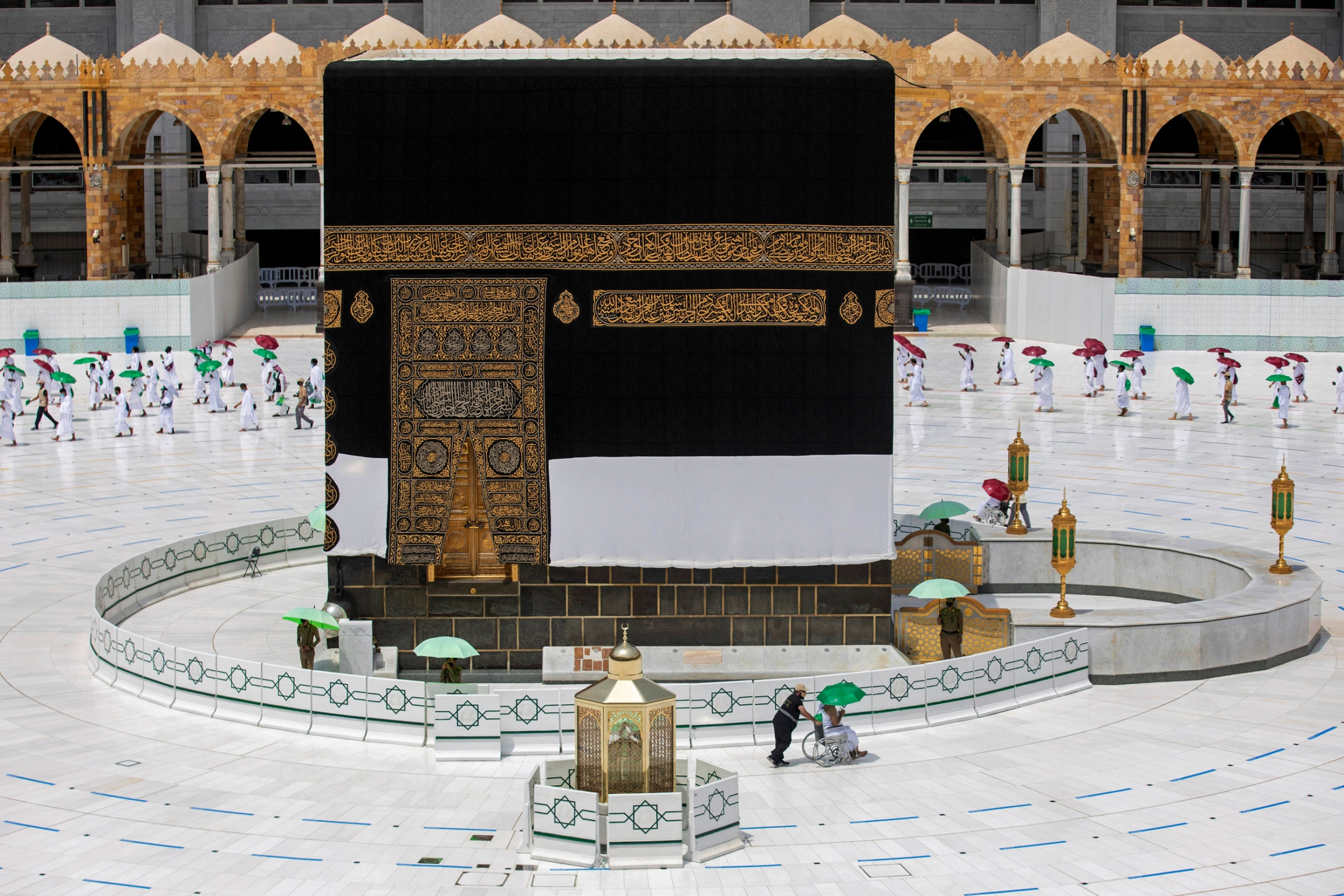 The cube-like Kaaba is shown center frame with a pilgrim being pushed in a wheelchair in the nearground.