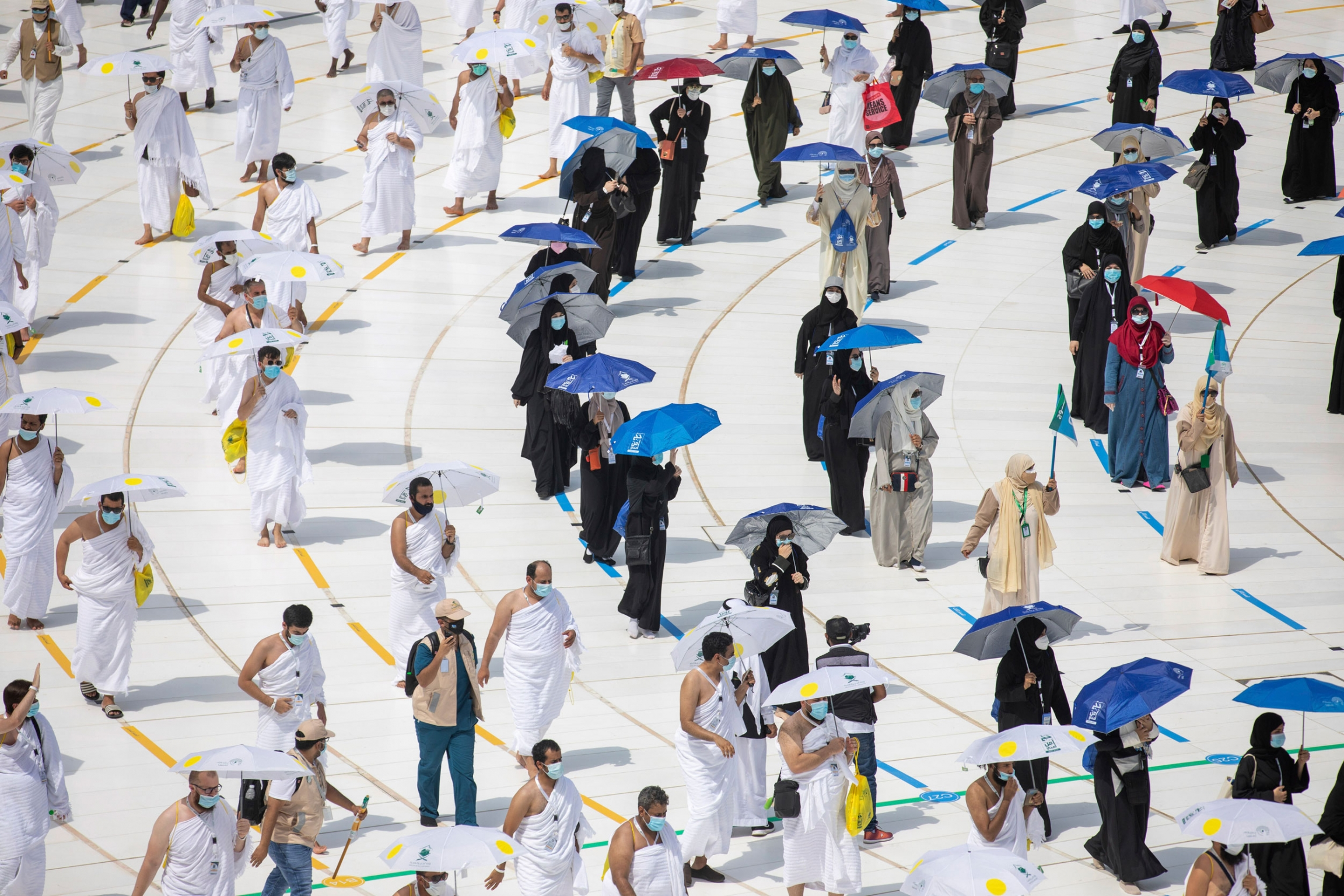 Pilgrims are shown walking on designated lines circuling the Kaaba.