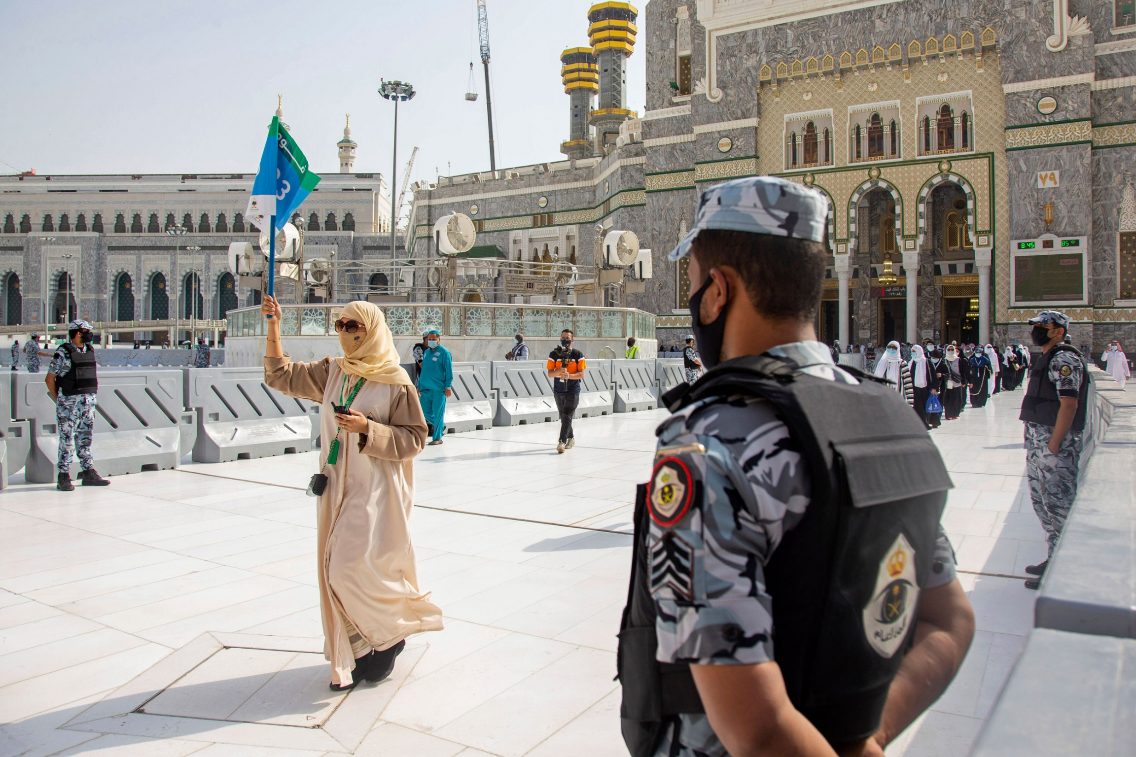 A security official is shown in the near ground with a woman in the distance walking and holding up a guide flag.