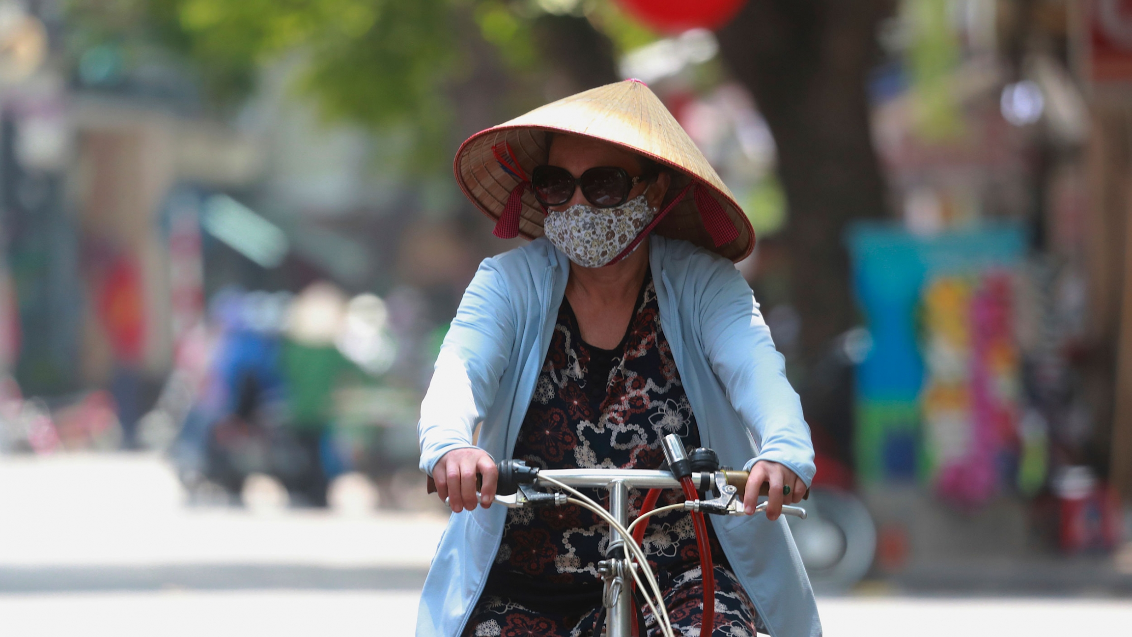 A woman is shown wearing a blue jacket, sunglasses, face mask and a straw hat while writing a bicycle.