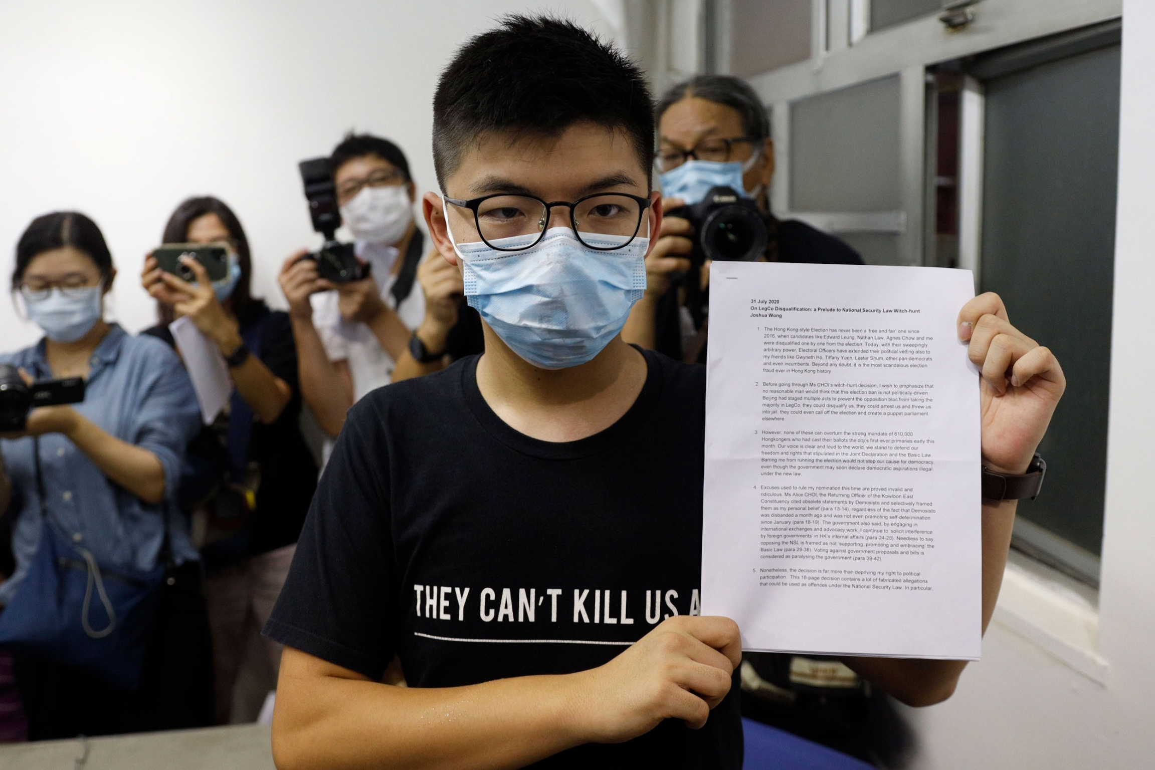 Hong Kong pro-democracy activist Joshua Wong is shown wearing a face mask a glasses while holding a white document up to the camera.