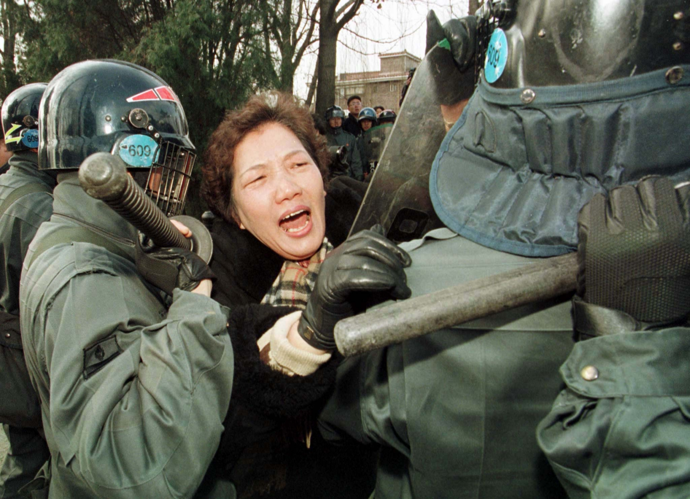 A woman protester cries out amid riot police in green uniforms.