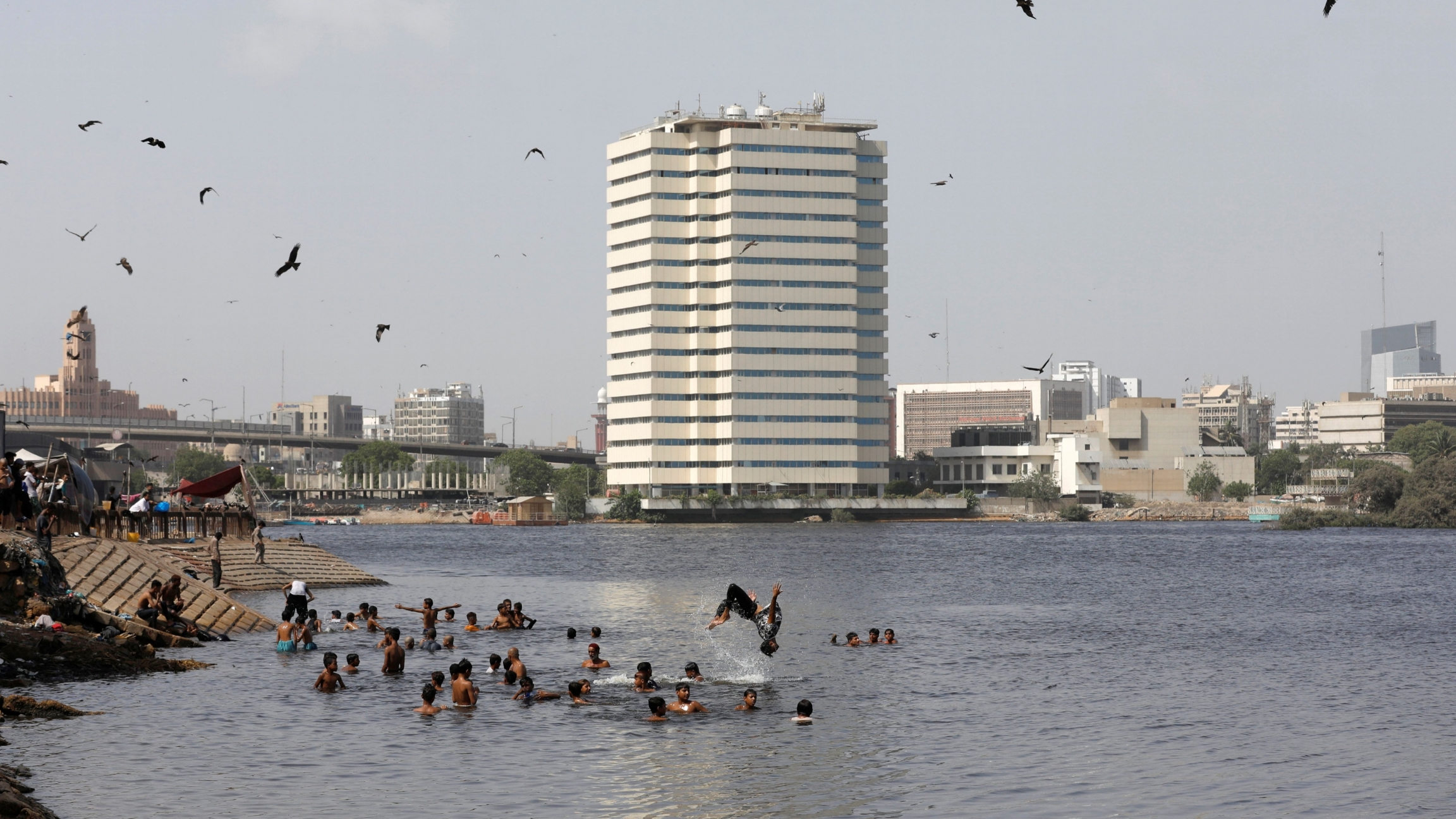 Adults and children swim in water near a large, white building in the background and birds flying overhead