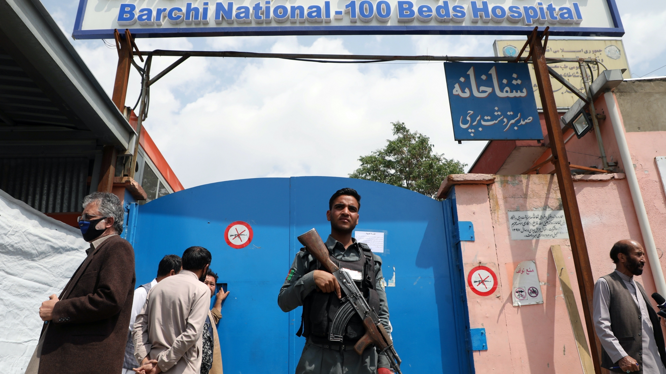A man with a gun stands in front of a blue door of a hospital that got attacked.