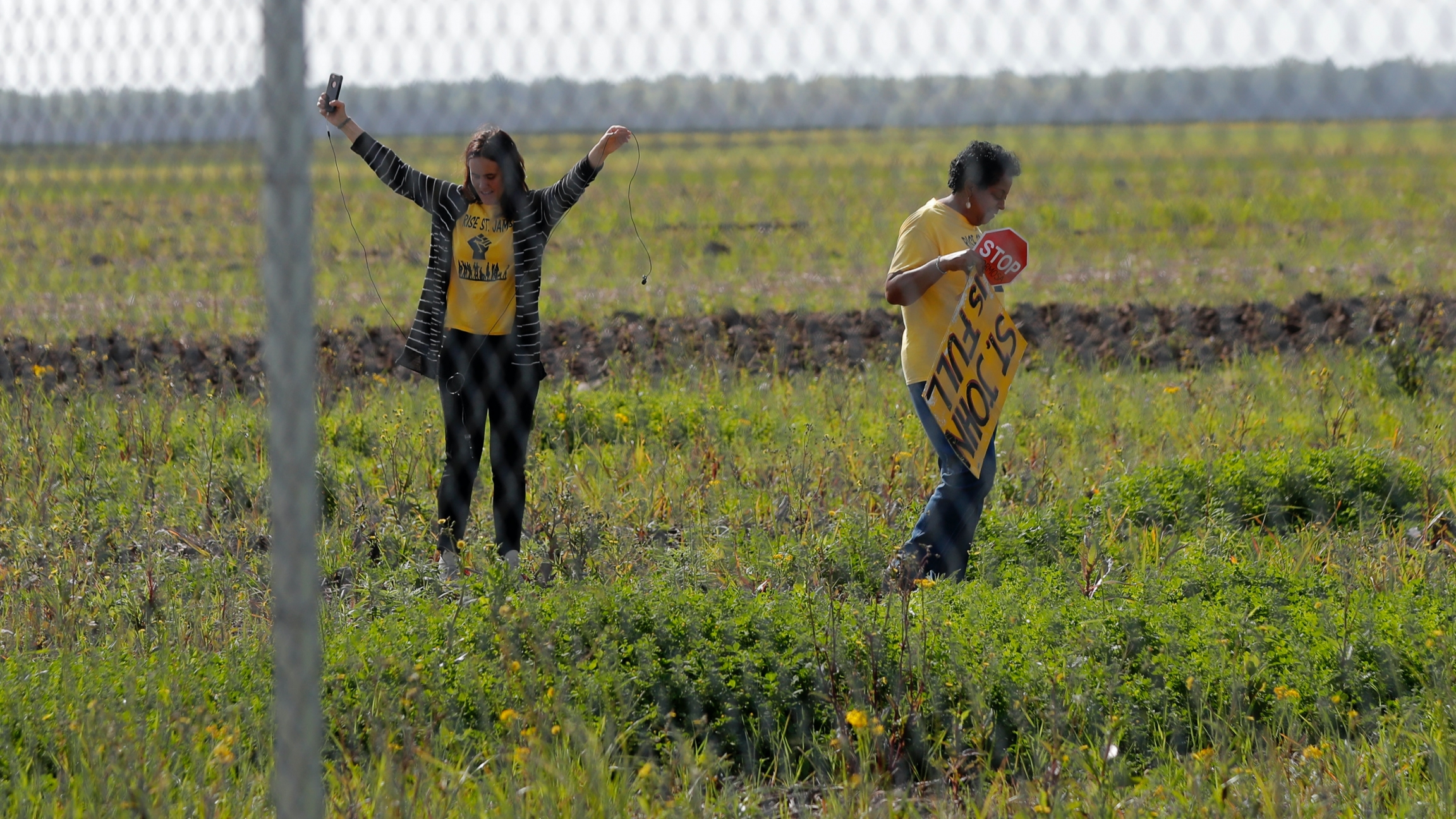 Two Black American women wearing yellow activist shirts stand in a field behind a fence