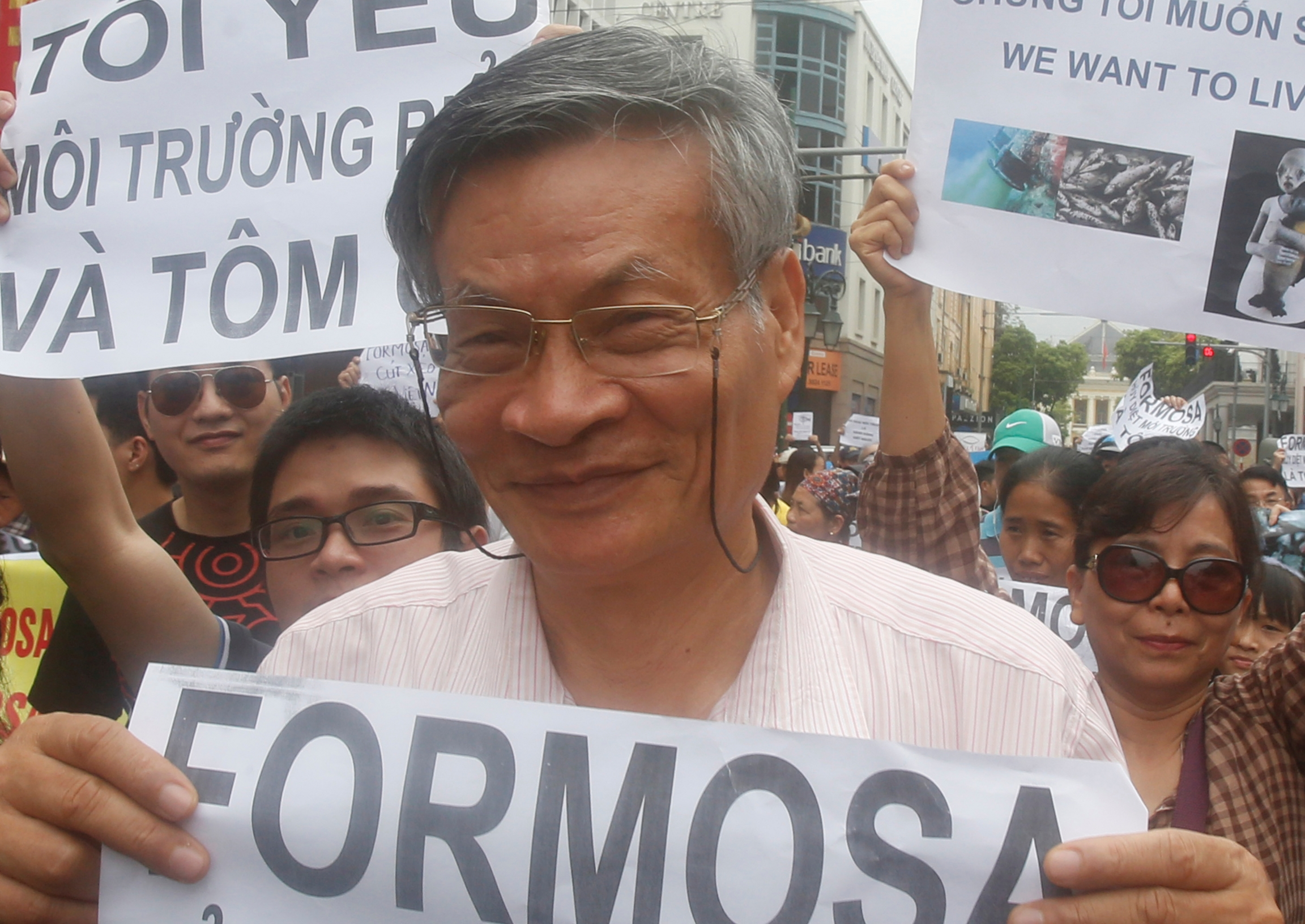 A man holds a protest sign in a large crowd against Formosa Plastics