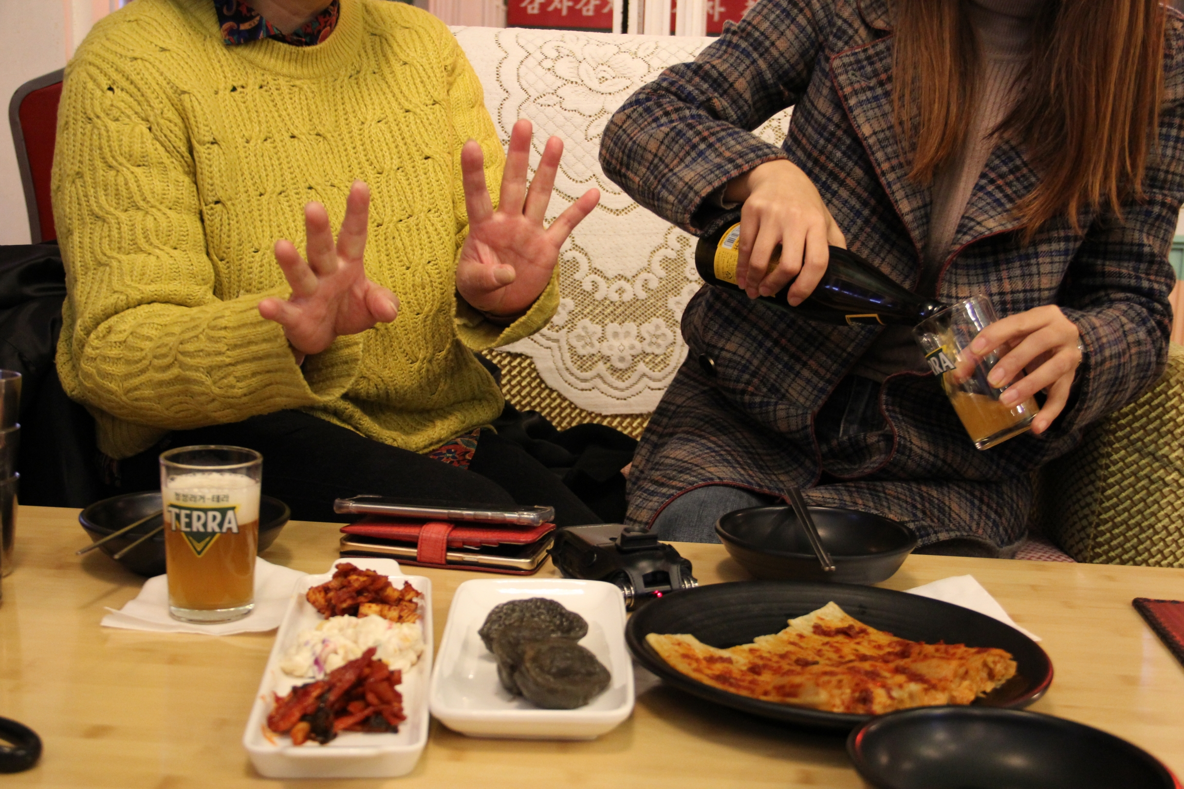 Kim Eun-joo (right) does Han (left) the courtesy of pouring a glass of beer before they begin eating dinner.