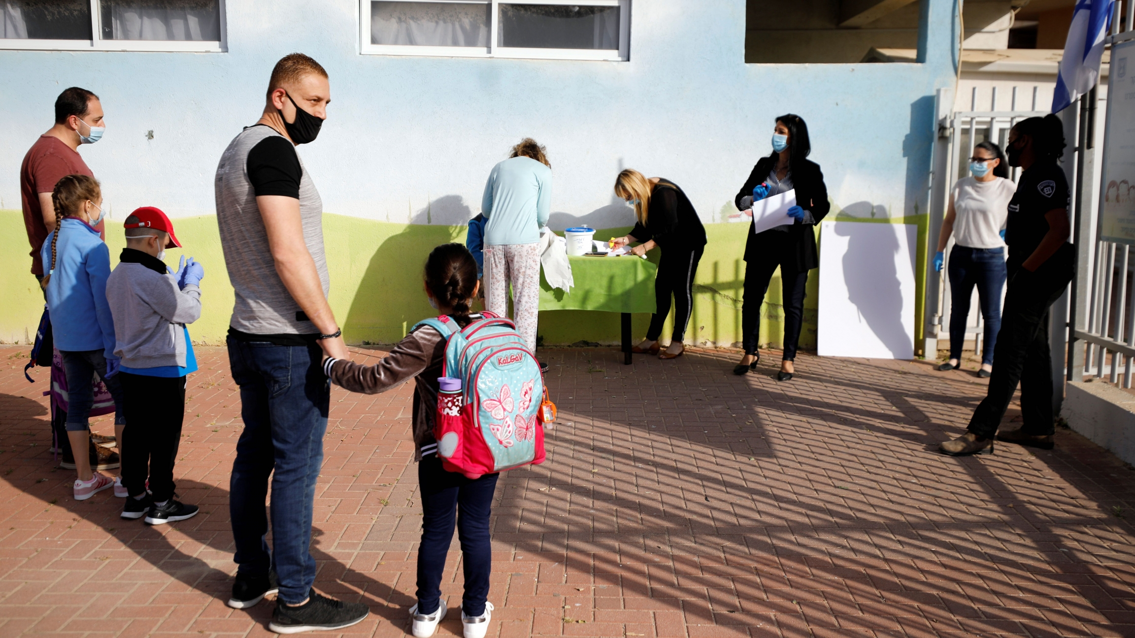 Parents wait with their children to enter their elementary school in Sderot as it reopens following the ease of restrictions preventing the spread of the coronavirus in Israel, May 3, 2020.