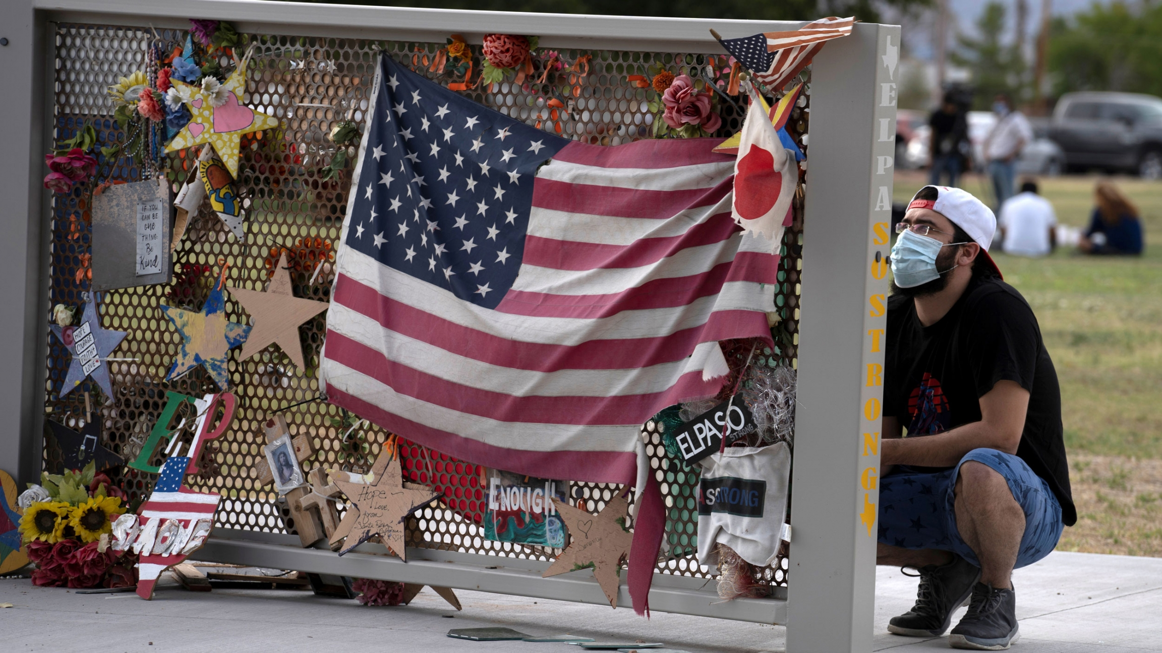 A man is shown kneeling next to a memorial that has stars and an American flag pinned on it.