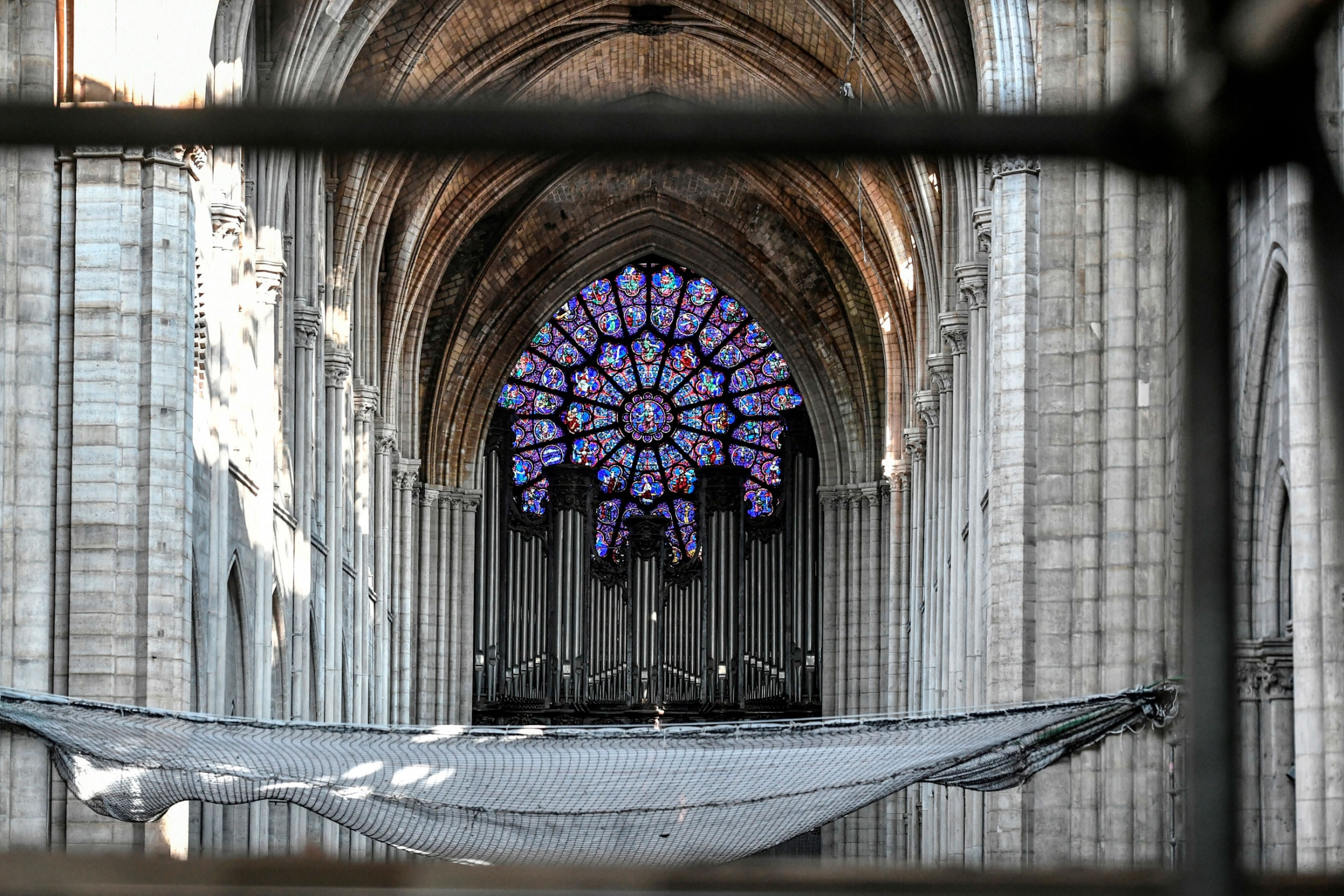 A wall of silver pipes are shown underneath stained-glass windows  in the santuary of Notre-Dame cathedral.