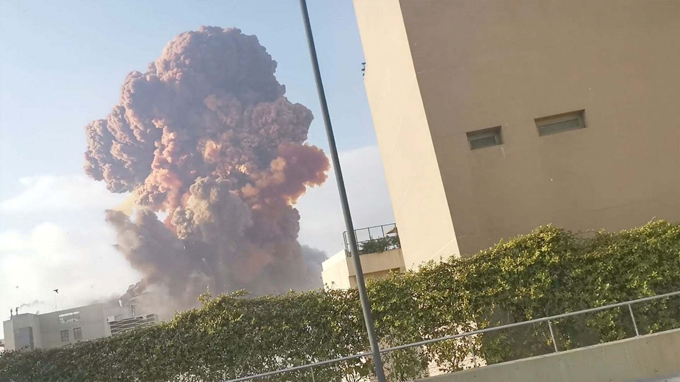 The dark plume of an explosion rises in the distance with a khaki-colored building in the nearground.