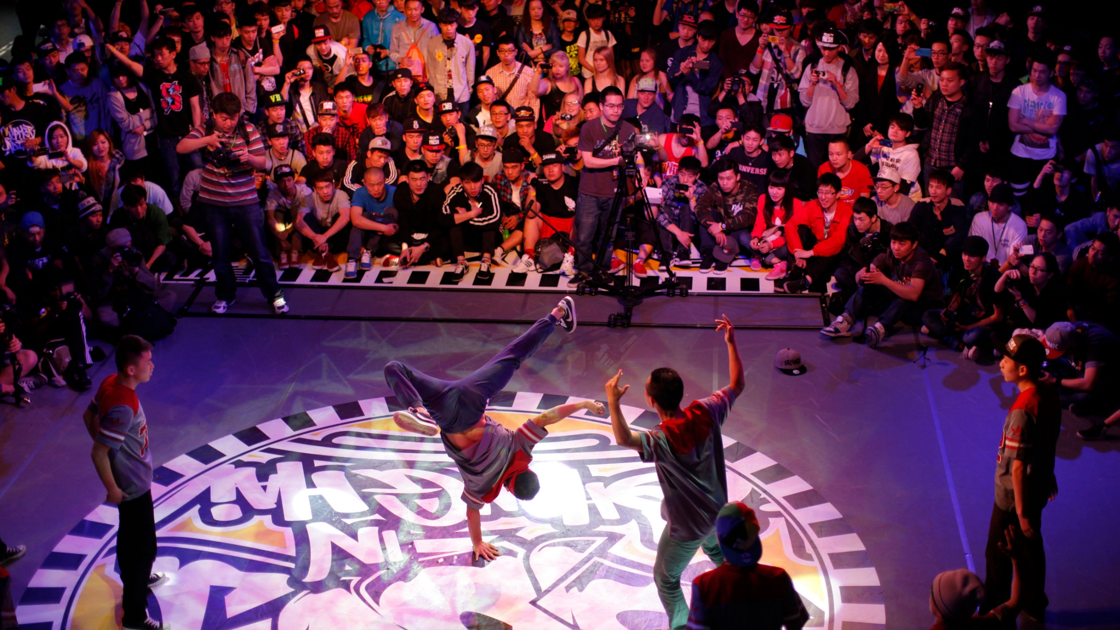 Several breakdancers perform on stage with a large crowd watching.