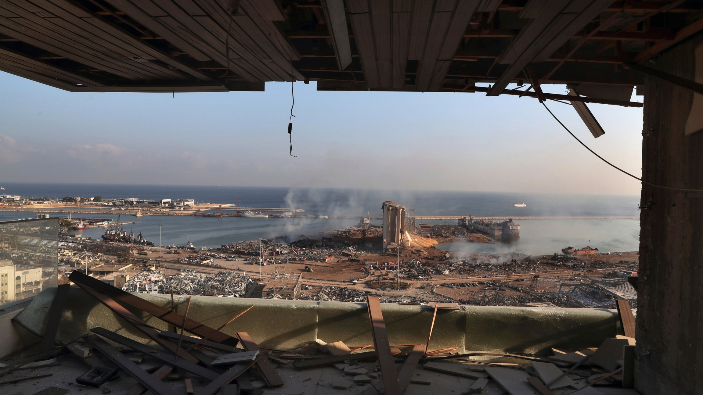 A view of the site of an explosion in the port of Beirut with buildings turned to rubble and shown from inside a facility with it's window blown out.