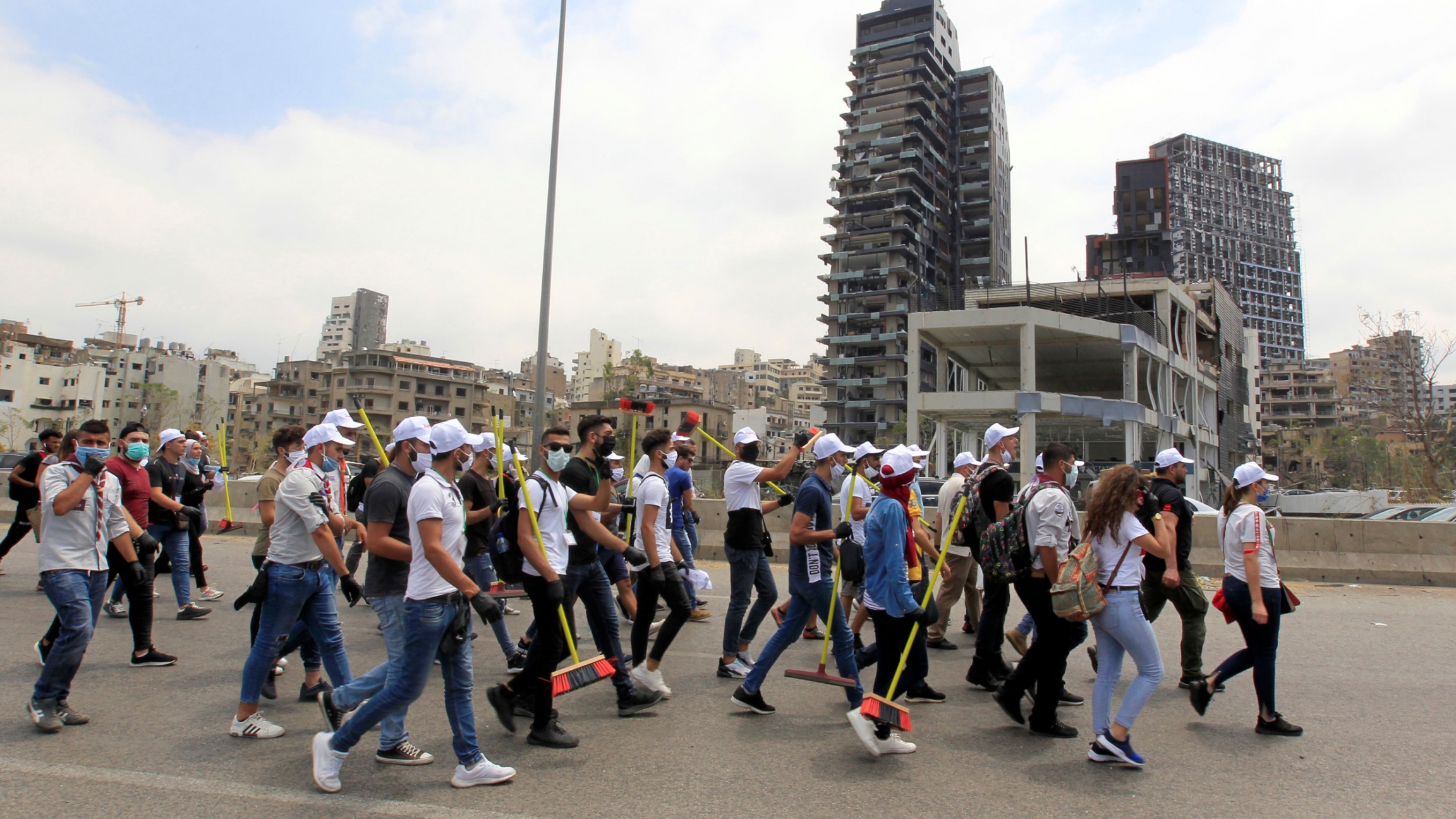 A crowd of people are shown walking in a street with many carrying a broom.