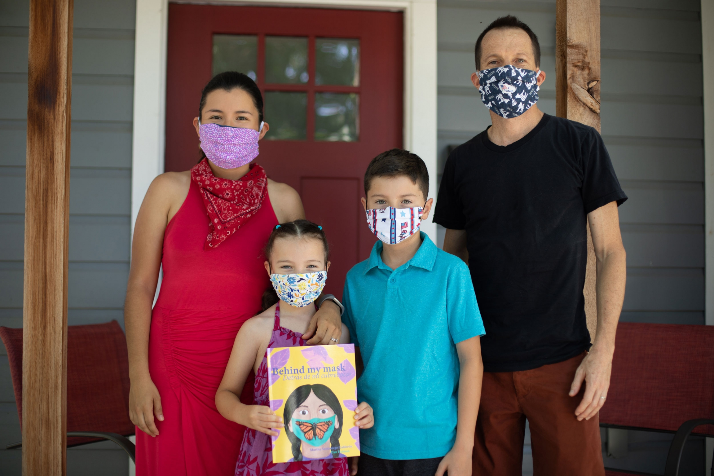 A family of four pose for a photo wearing masks. The young girl holds a book in her hands.